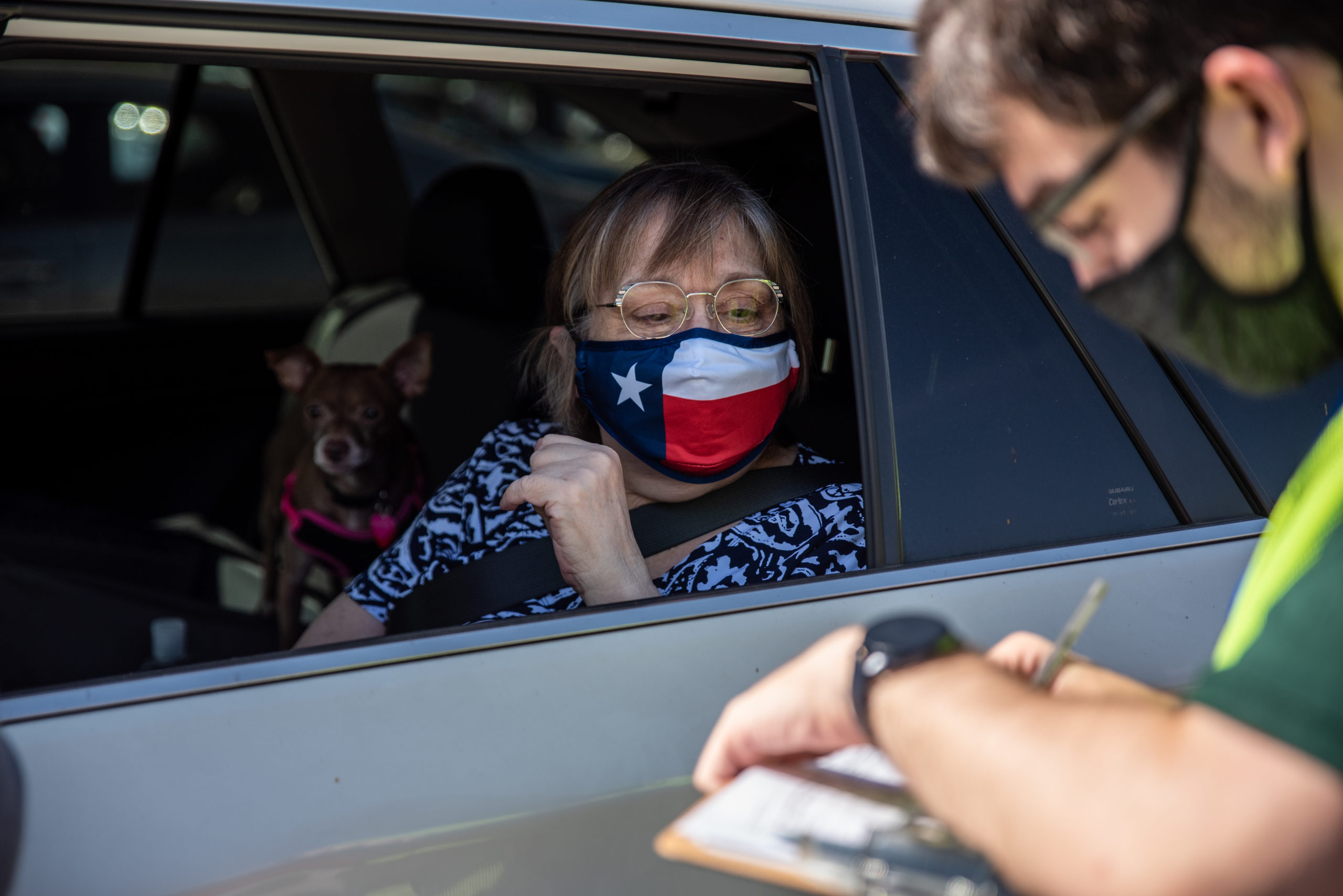 A poll worker helps a voter at a mail-in ballot drop off location on Oct. 13 in Austin, Texas. (Sergio Flores/Getty Images)