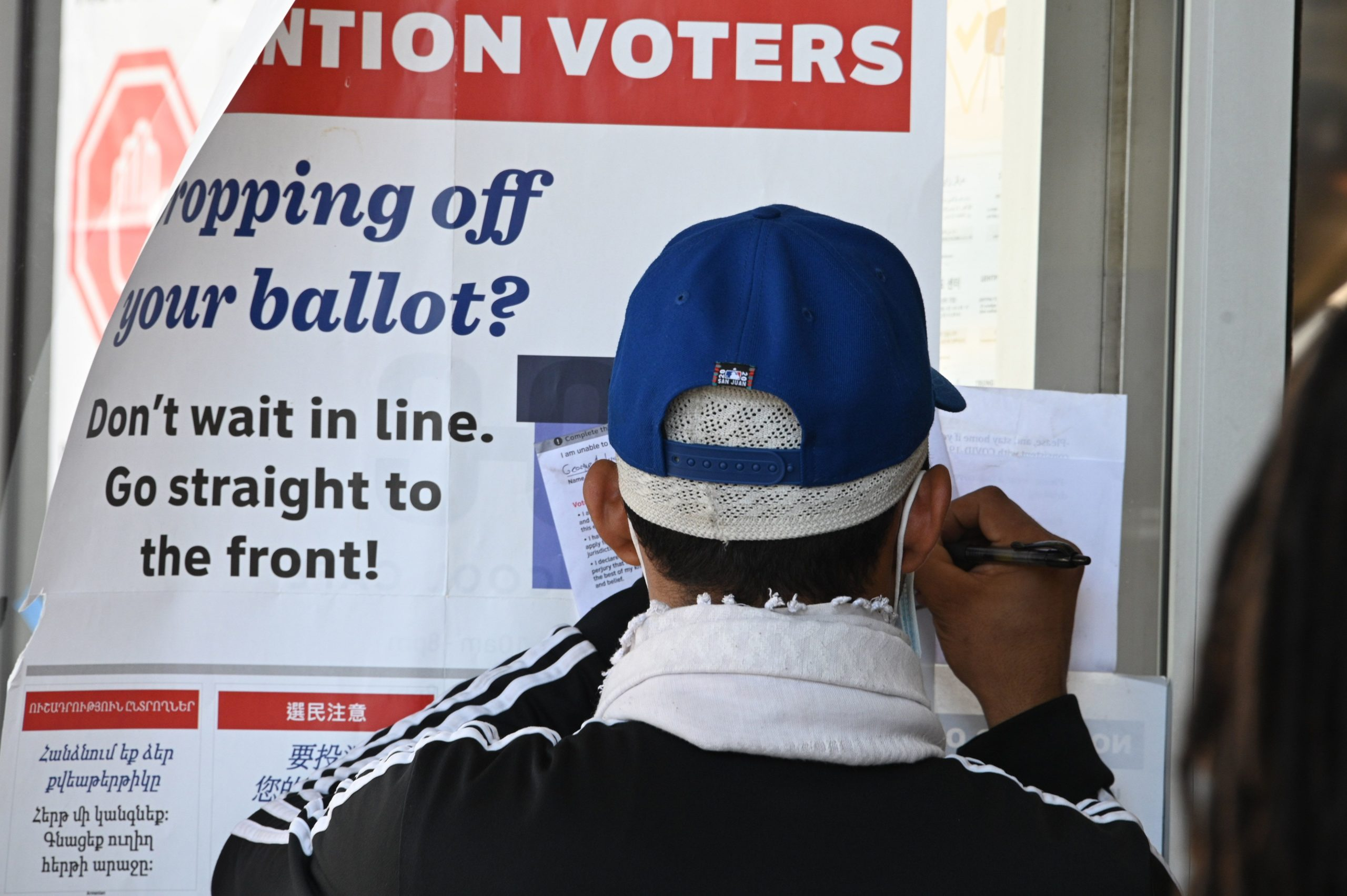 A man signs the back of his mail-in ballot before dropping it off at the vote center at the Hot & Cold Cafe in the Leimert Park neighborhood of Los Angeles, California on November 3, 2020. - Americans were voting on Tuesday under the shadow of a surging coronavirus pandemic to decide whether to reelect Republican Donald Trump, one of the most polarizing presidents in US history, or send Democrat Joe Biden to the White House. (Photo by Robyn Beck / AFP) (Photo by ROBYN BECK/AFP via Getty Images)