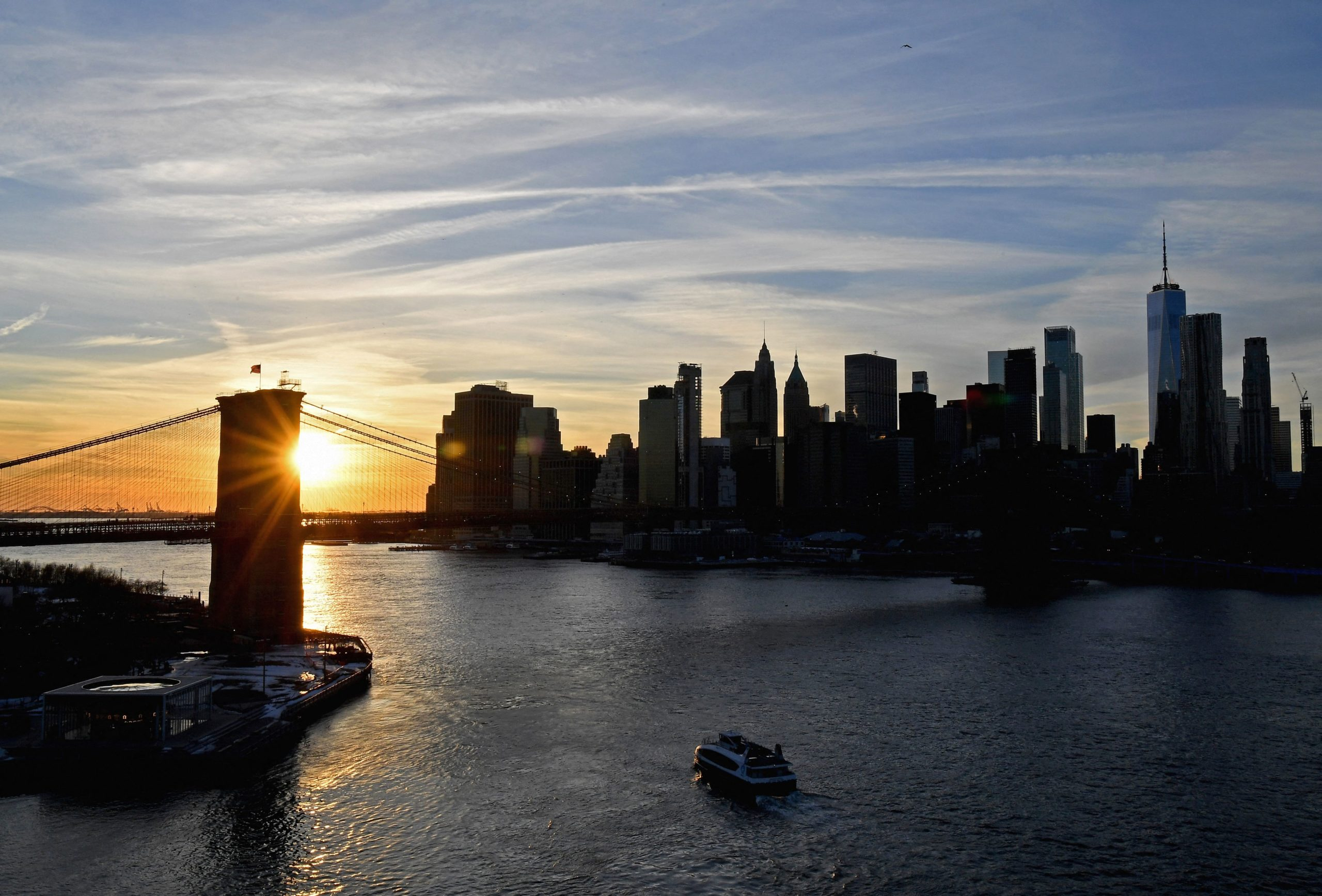 The sun sets behind Brooklyn bridge and skyline of lower Manhattan on February 17, 2021 in New York City. (Anglea Weiss/AFP via Getty Images)