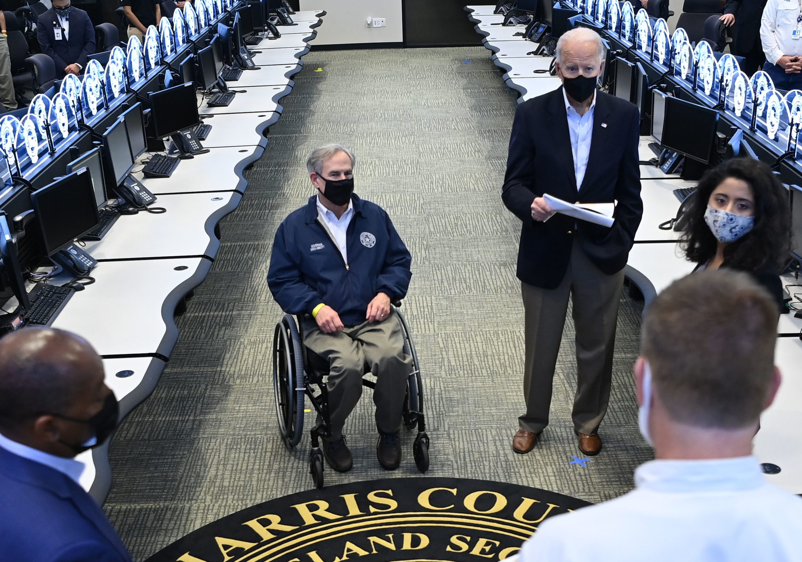 US President Joe Biden and Texas Governor Greg Abbott (L) listen to officials at the Harris County Emergency Operations Center in Houston, Texas on February 26, 2021. - Biden is visiting Houston, Texas following severe winter storms which left much of the state without electricity for days. (Photo by MANDEL NGAN/AFP via Getty Images)