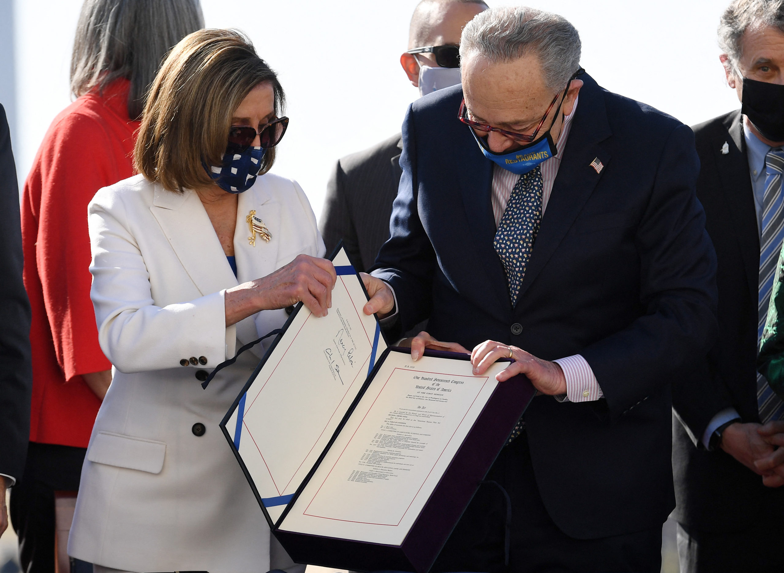 Speaker of the House Nancy Pelosi and Senate Majority Leader Chuck Schumer hold the signed American Rescue Plan Act on March 10. (Olivier Douliery/AFP via Getty Images)