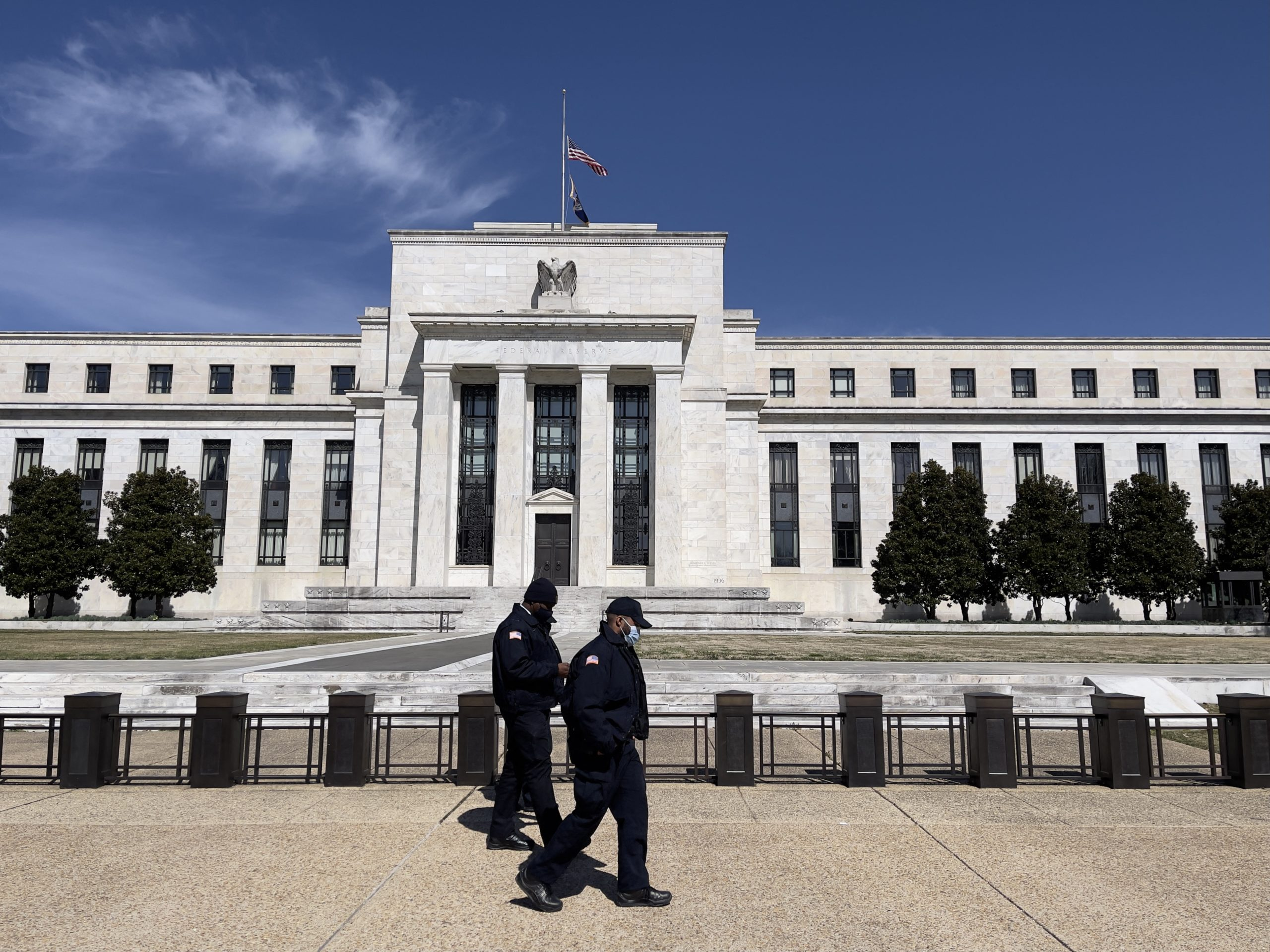 People walk past the Federal Reserve on March 19 in Washington, D.C. (Daniel Slim/AFP via Getty Images)