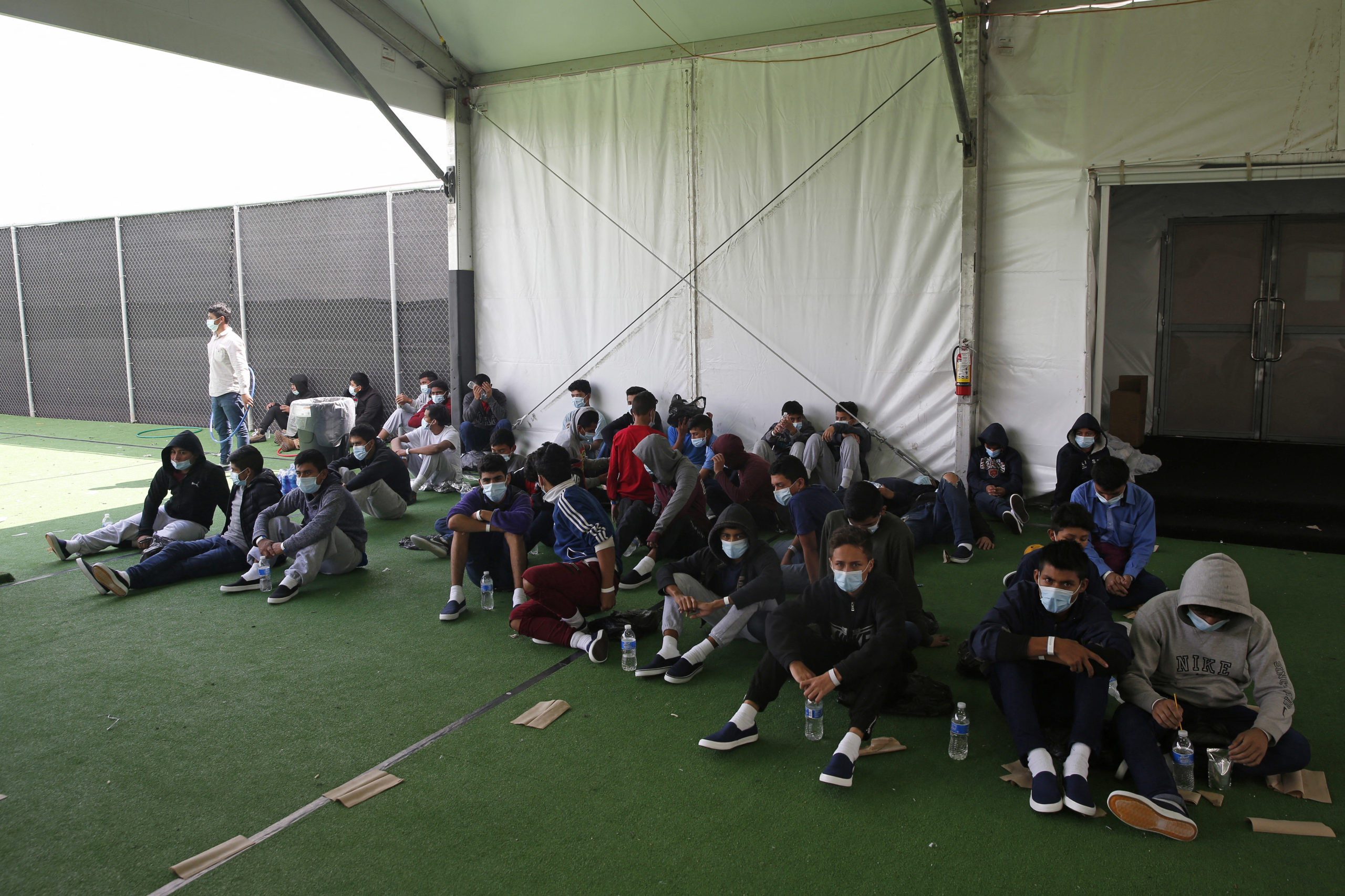 Young minors who tested positive for Covid-19 sit in the ground at the Donna Department of Homeland Security holding facility, the main detention center for unaccompanied children in the Rio Grande Valley run by the US Customs and Border Protection. (Photo by DARIO LOPEZ-MILLS/POOL/AFP via Getty Images)