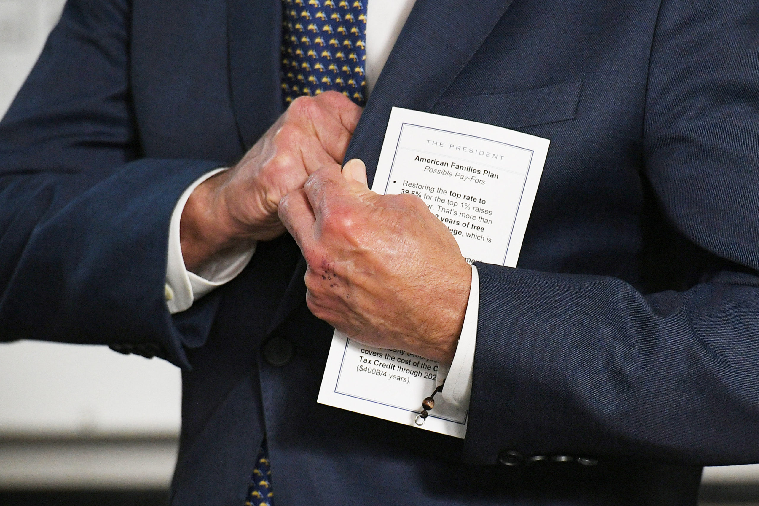 President Joe Biden holds a note card about the American Families plan while being introduced on May 3. (Mandel Ngan/AFP via Getty Images)