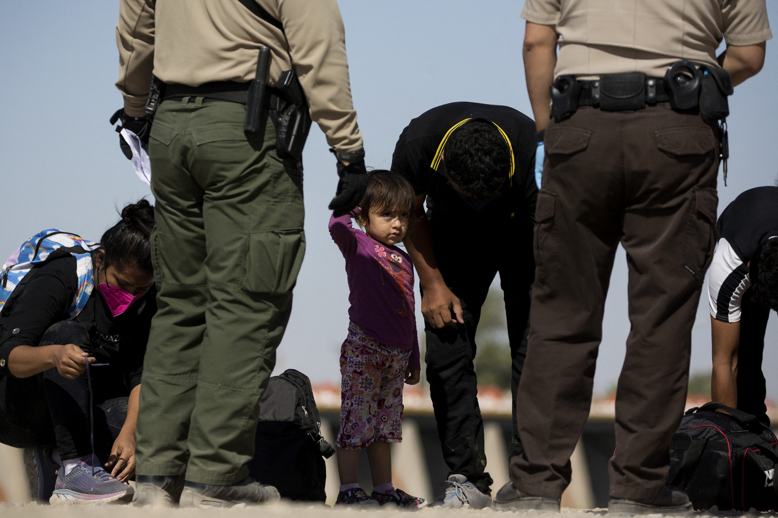 A girl looks on as migrants from Guatemala remove their shoelaces as they are initially processed after turning themselves over to authorities at the US-Mexico border May 12, 2021 in Yuma, Arizona (Photo by RINGO CHIU/AFP via Getty Images)