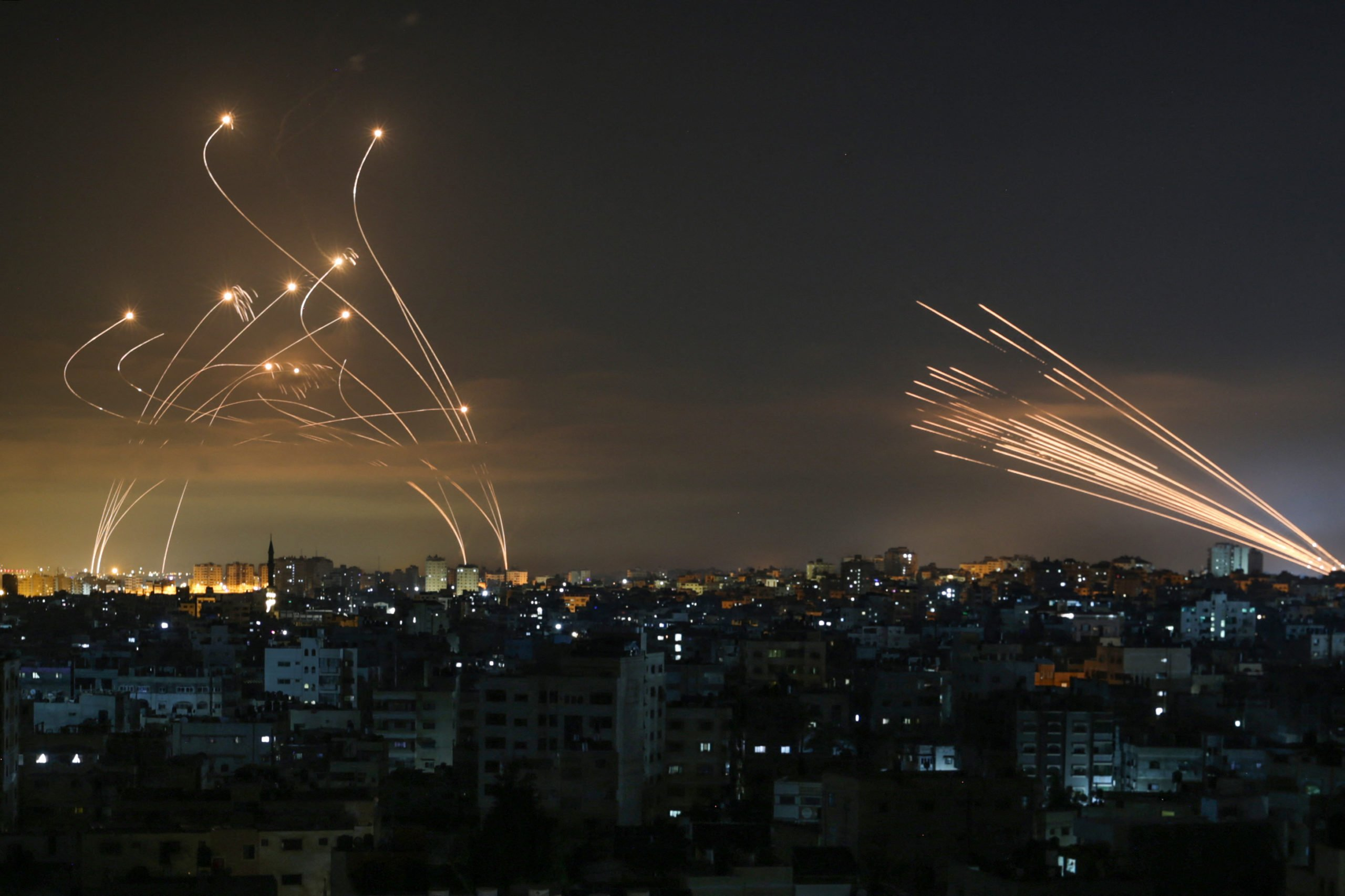 The Israeli Iron Dome missile defence system (L) intercepts rockets (R) fired by the Hamas movement towards southern Israel from Beit Lahia in the northern Gaza Strip as seen in the sky above the Gaza Strip overnight on May 14, 2021. (Photo by ANAS BABA/AFP via Getty Images)