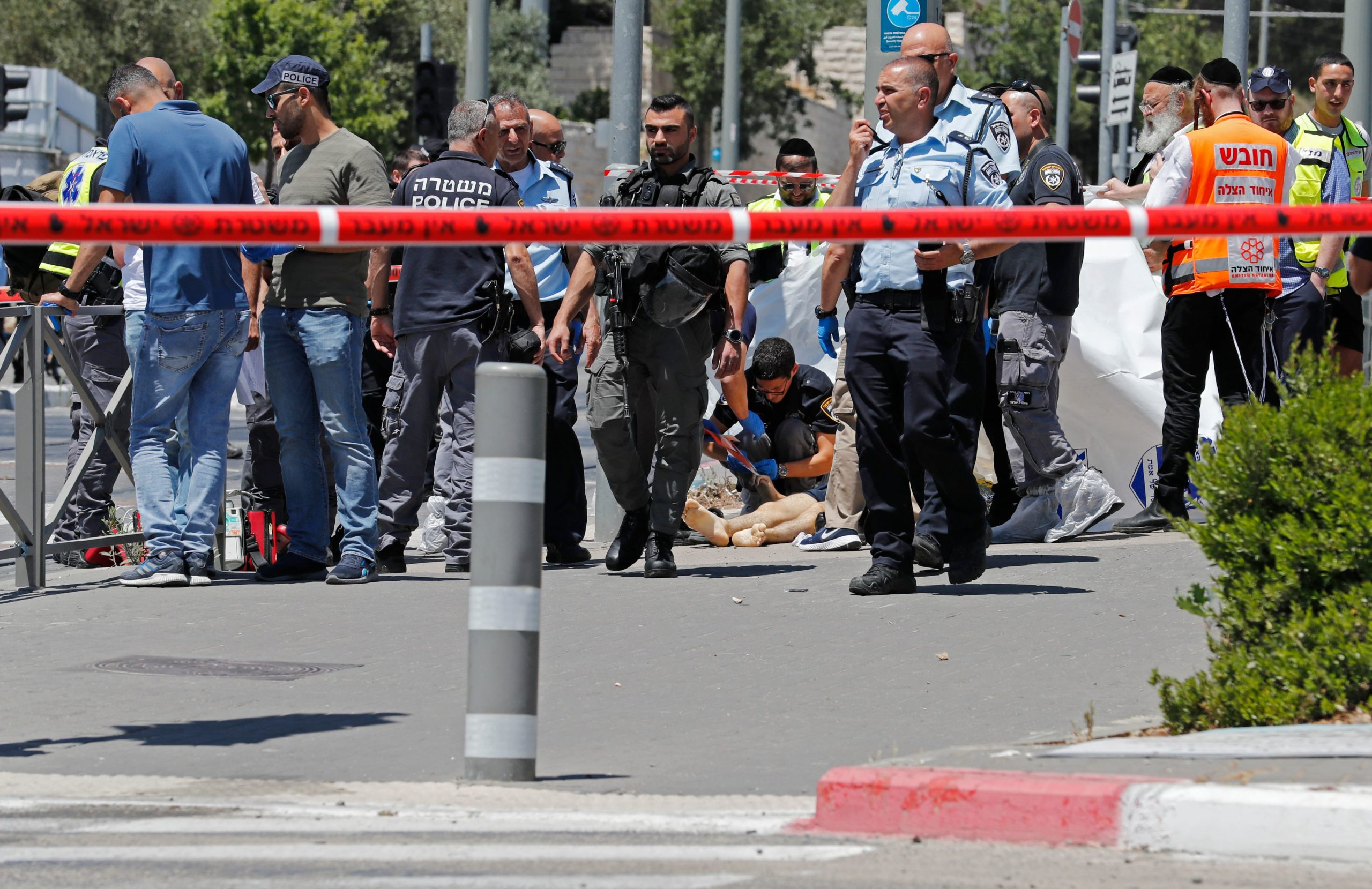 Israeli security forces and emergency services gather around the body of a suspected attacker at the site of a reported stabbing attack near the Sheikh Jarrah neighbourhood in Israeli-annexed east Jerusalem, on May 24, 2021. (Photo by Ahmad GHARABLI / AFP) (Photo by AHMAD GHARABLI/AFP via Getty Images)