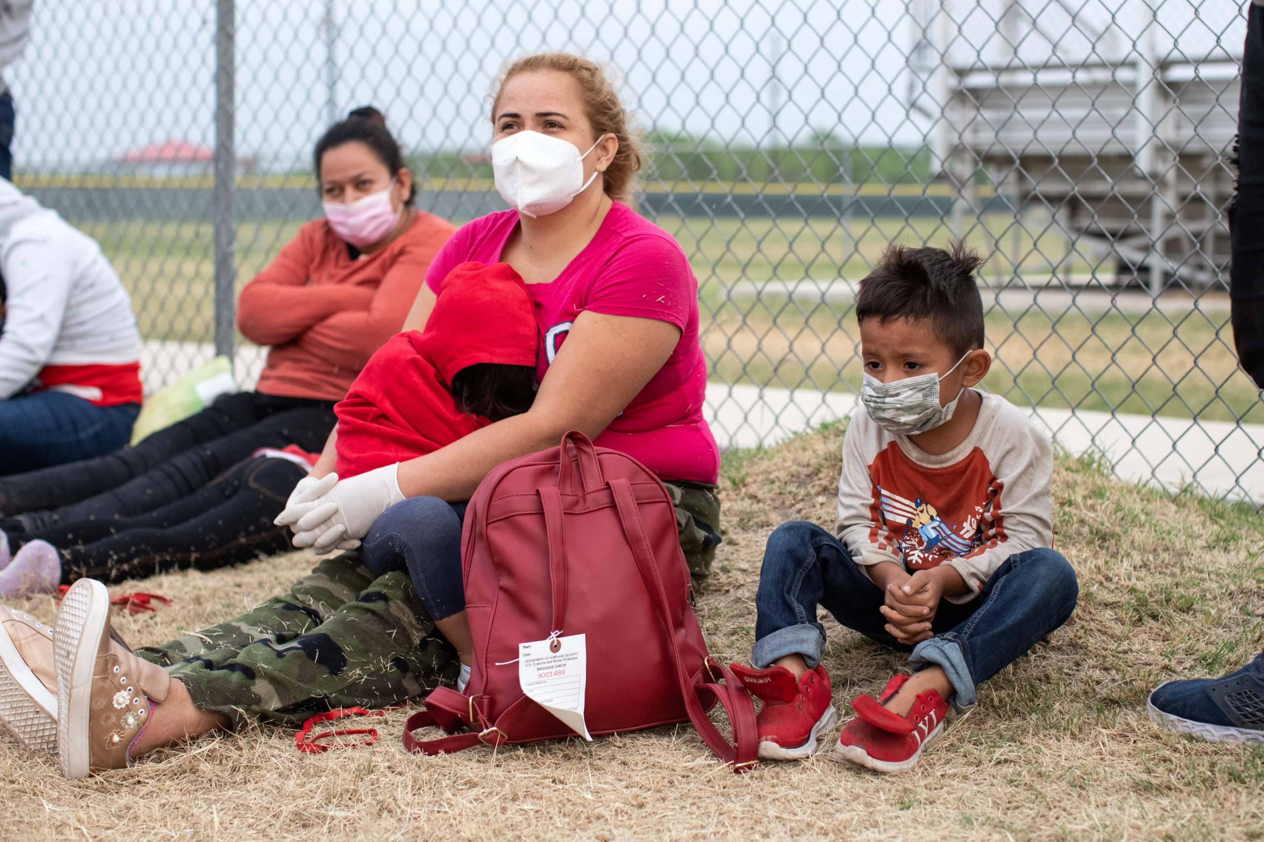 Several illegal migrants waited on the grass near the side of a public road as Customs and Border Protection officials worked to process the groups in La Joya, Texas on March 27, 2021. (Kaylee Greenlee - Daily Caller News Foundation)