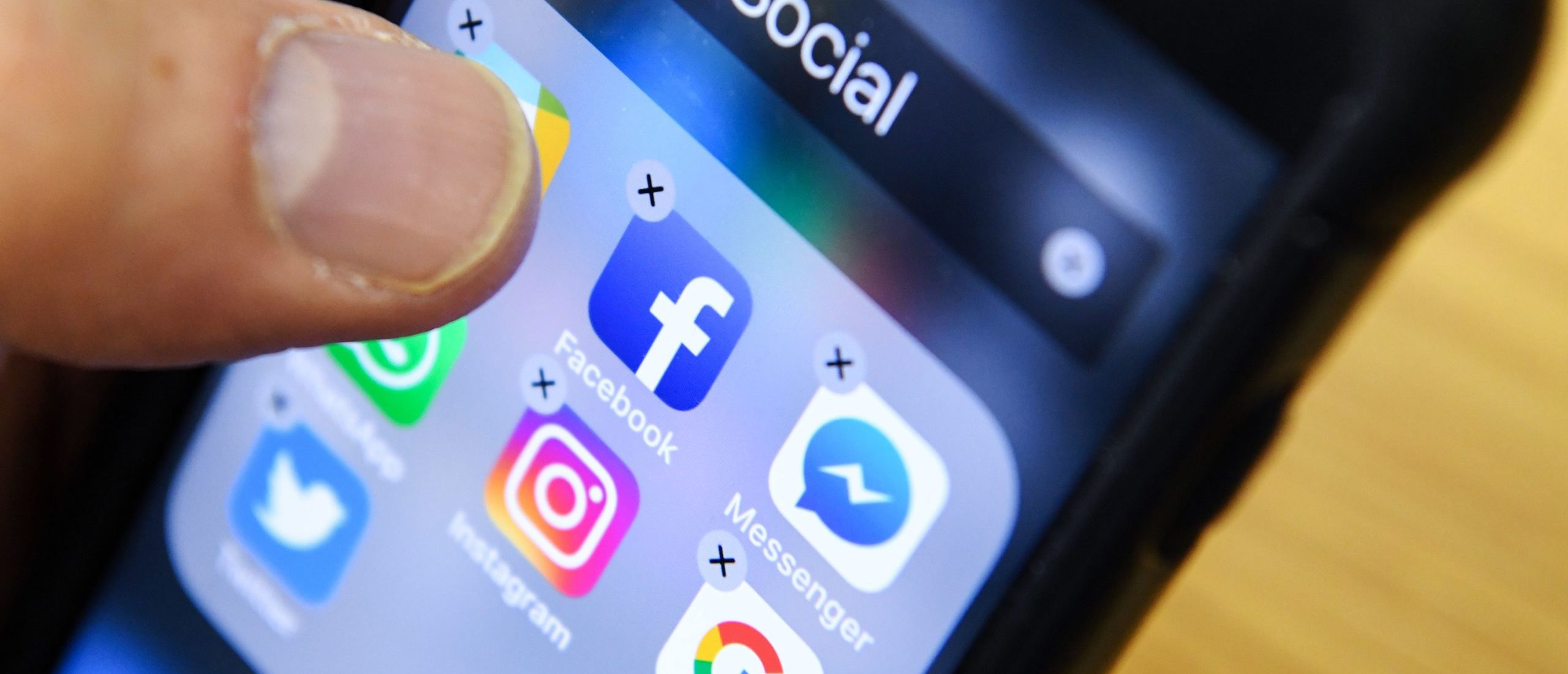 A man holds a smart phone with the icons for the social networking apps Facebook, Instagram and Twitter seen on the screen in Moscow on March 23, 2018. (KIRILL KUDRYAVTSEV/AFP via Getty Images)