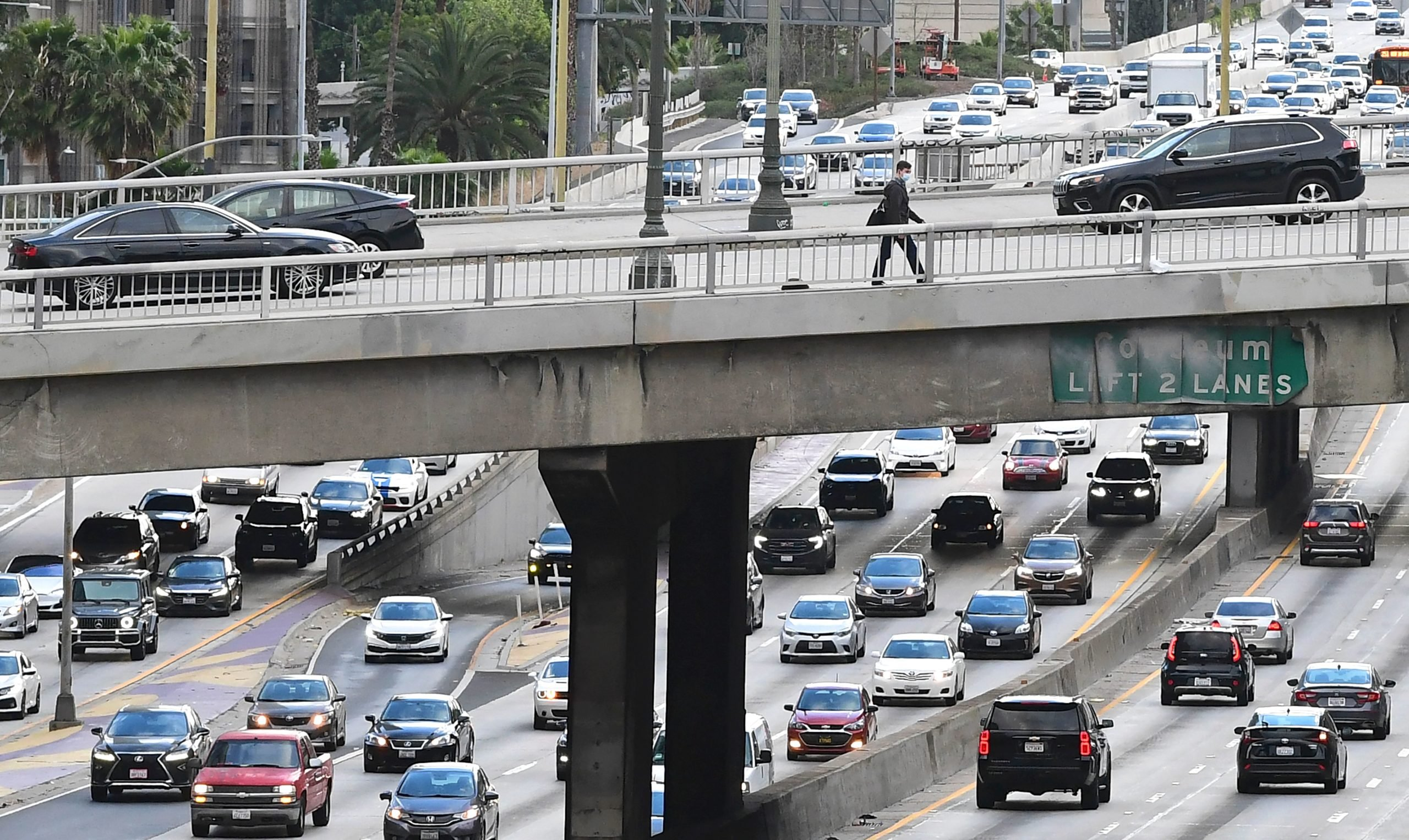 A pedestrian crosses an overpass above afternoon rush hour traffic in Los Angeles, California on April 26, 2021. (Photo by Frederic J. BROWN / AFP via Getty Images)