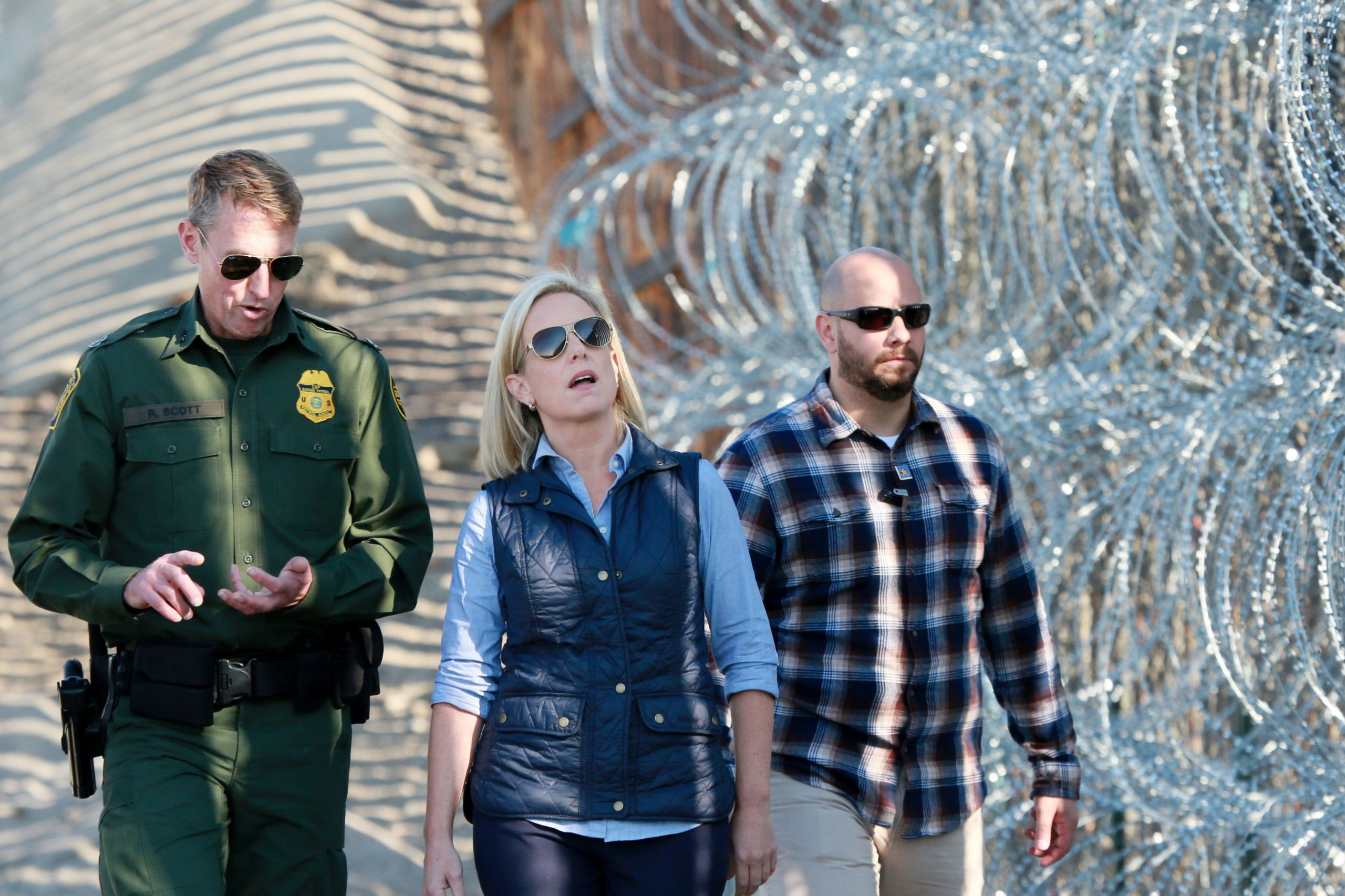 Kirstjen M. Nielsen, Secretary of the Department of Homeland Security, tours the border area with San Diego Section Border Patrol Chief Rodney Scott (L) at Borderfield State Park along the United States-Mexico Border fence in San Ysidro, California on November 20, 2018. (Photo credit should read SANDY HUFFAKER/AFP via Getty Images)