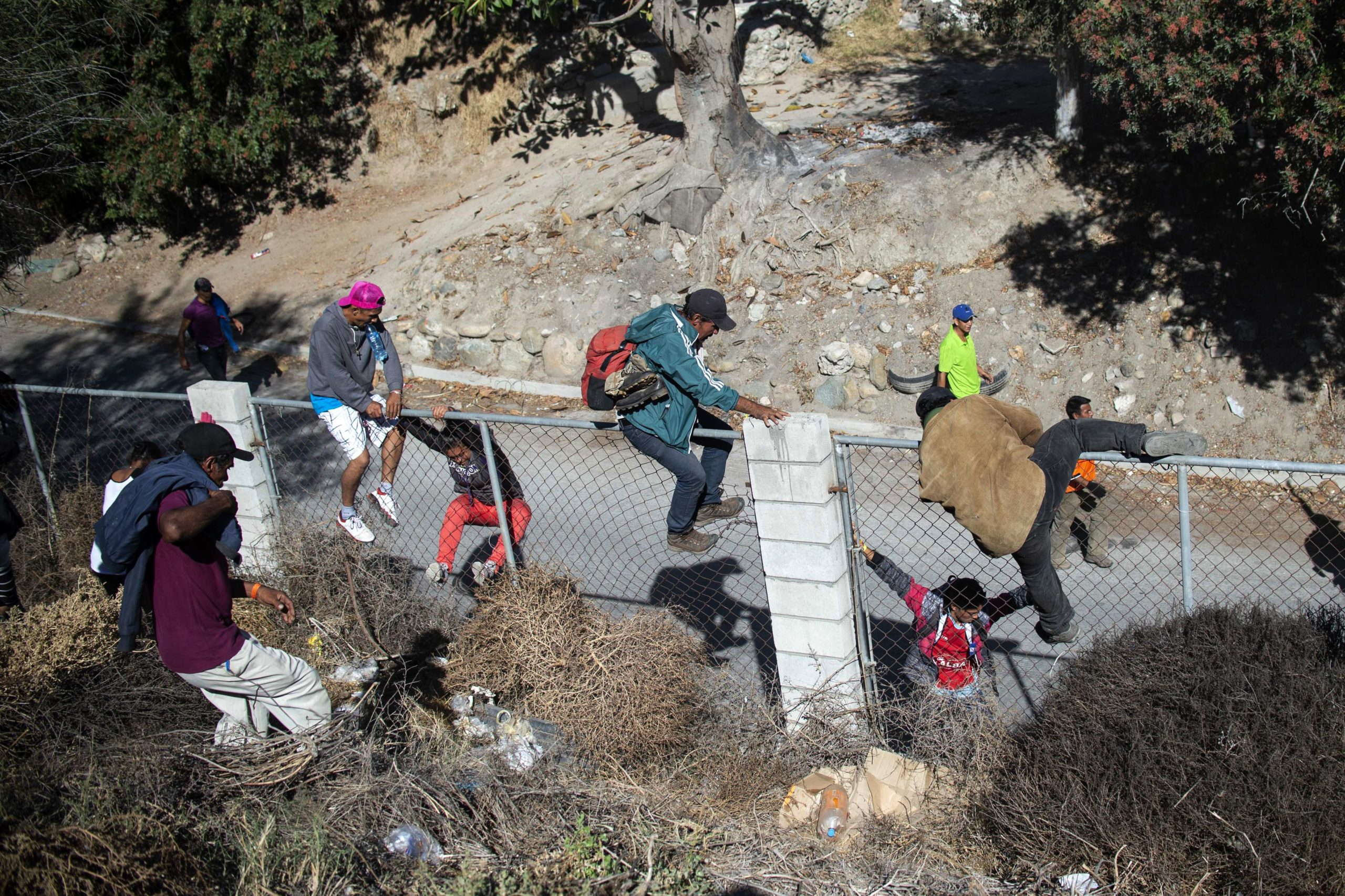 A group of Central American migrants -mostly from Honduras- cross over a fence as they try to reach the border fence between Mexico and the United States, in Tijuana, Baja California State, Mexico, near US-Mexico border on November 25, 2018. (Photo credit should read PEDRO PARDO/AFP via Getty Images)