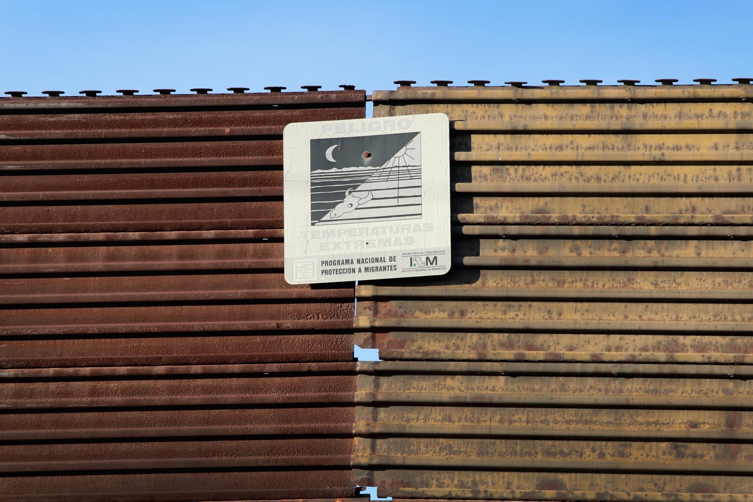 A sign hanging on the Mexico side of the border wall that separates the United States from Mexico warns migrants of the dangers of travelling through the desert. (Photo by Scott Olson/Getty Images)