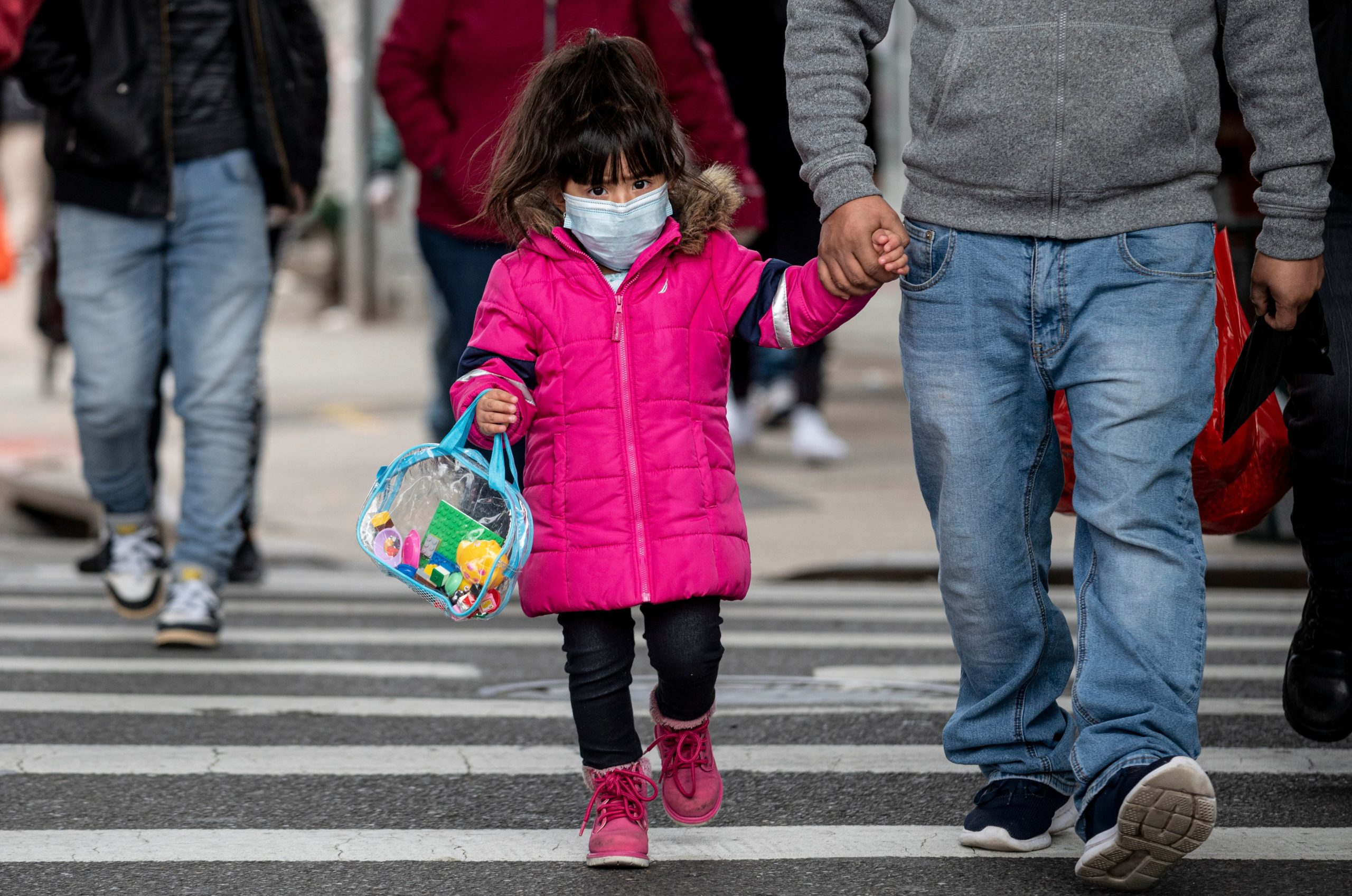 A girl, wearing a mask, walks down a street in the Corona neighborhood of Queens on April 14, 2020 in New York City. - New York will start making tens of thousands of coronavirus test kits a week, its mayor announced Tuesday, as the city looks to boost testing capacity with a view to ending its shutdown. (Photo by Johannes Eisele/AFP via Getty Images)