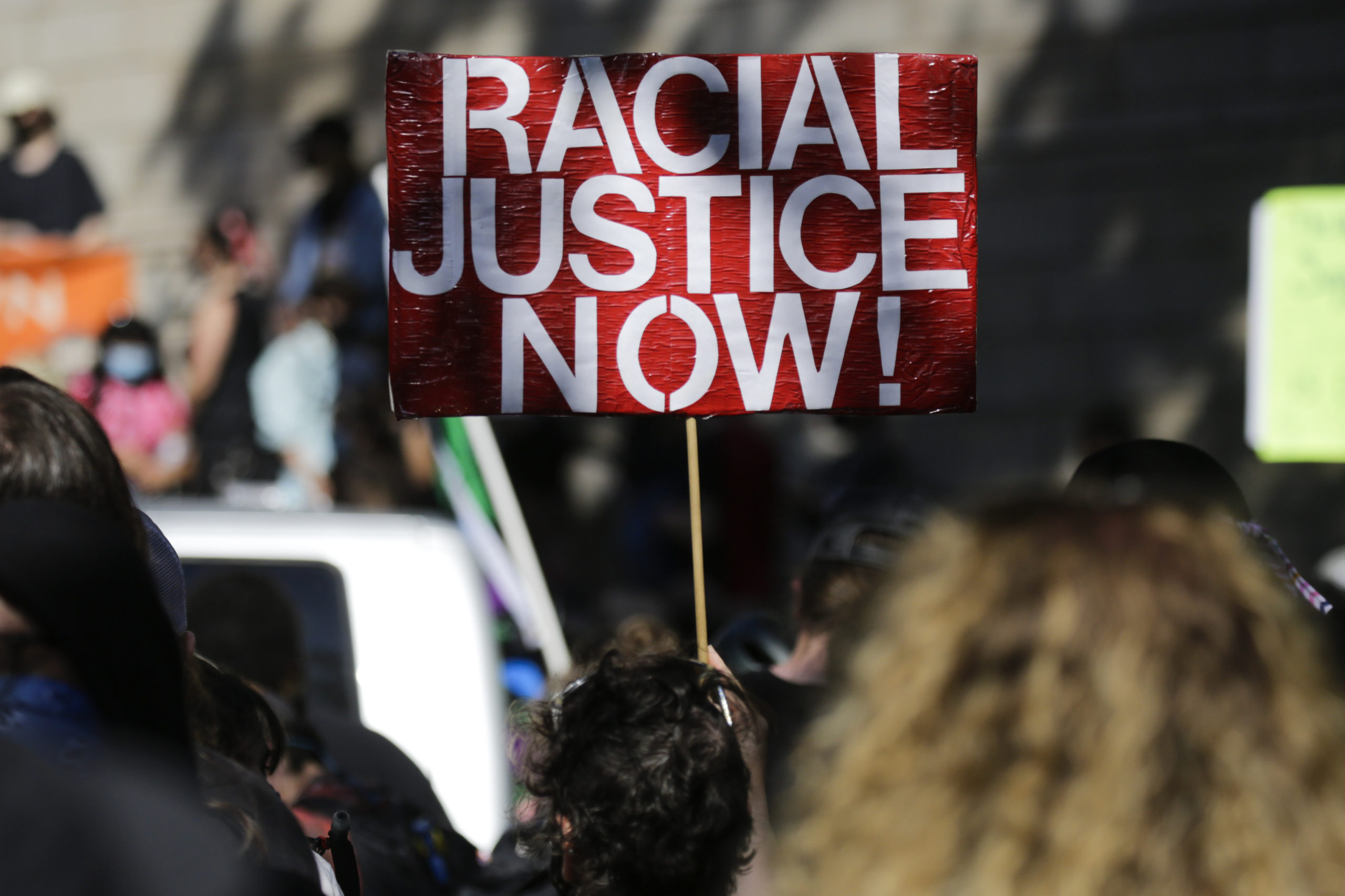 """A protestor holds a """"Racial Justice Now"""" sign during a """"Defund the Police"""" march from King County Youth Jail to City Hall in Seattle, Washington on August 5, 2020. (Photo by Jason Redmond / AFP) (Photo by JASON REDMOND/AFP via Getty Images)"""
