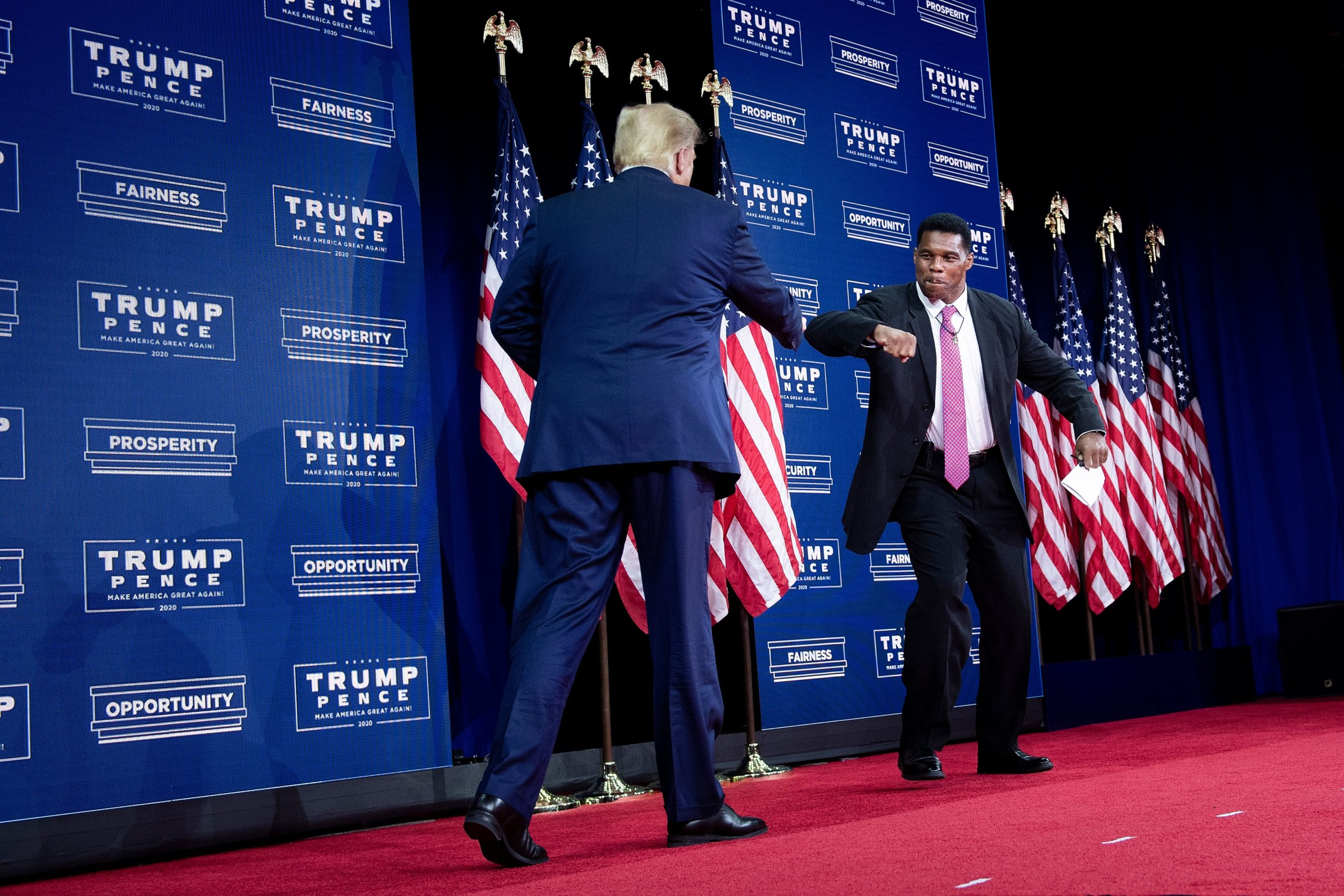 US President Donald Trump is greeted by NFL hall of fame member Herschel Walker during an event for black supporters at the Cobb Galleria Centre September 25, 2020, in Atlanta, Georgia. (Photo by BRENDAN SMIALOWSKI/AFP via Getty Images)