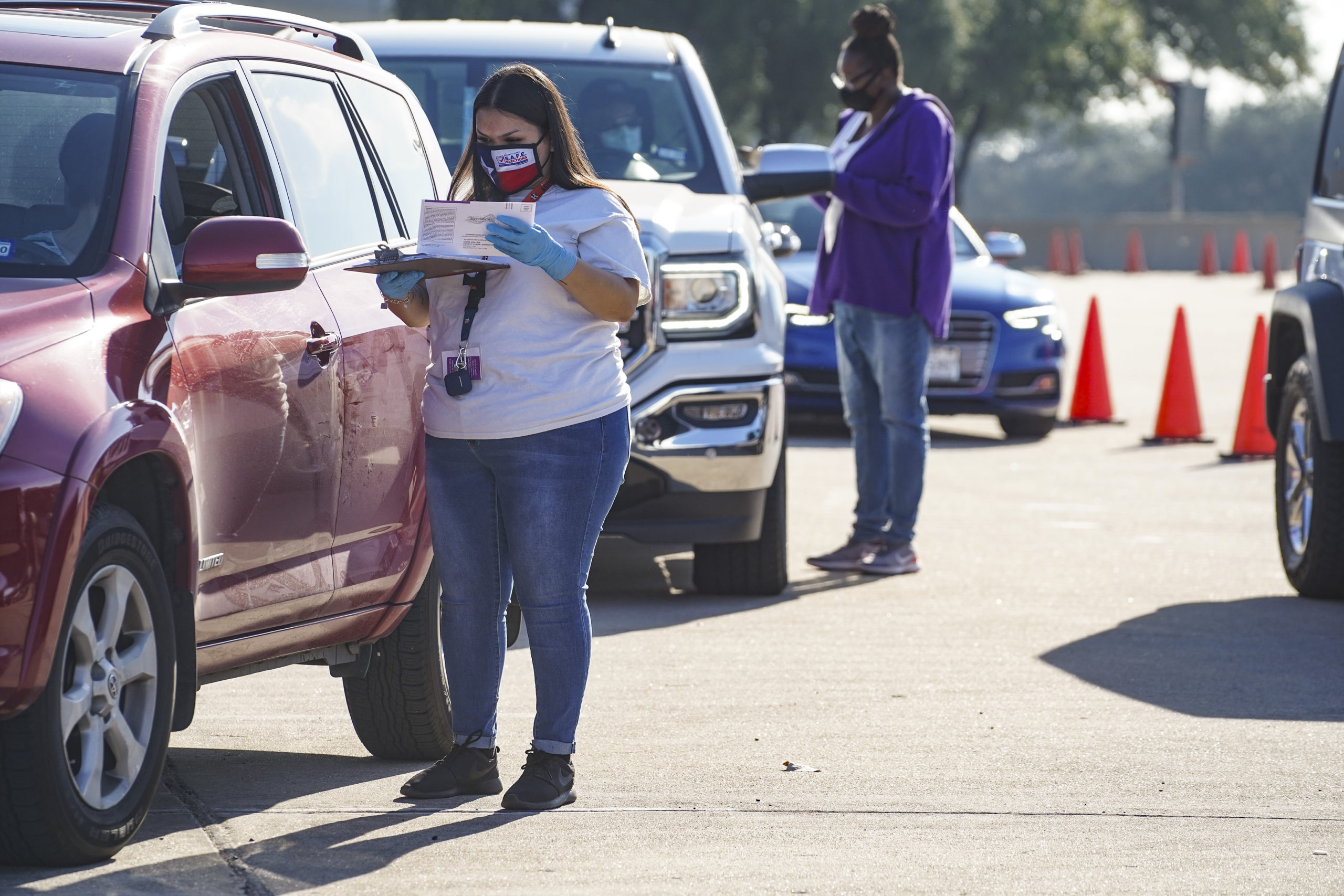 HOUSTON, TX - OCTOBER 07: Election workers accept mail in ballot from voters at drive-through mail ballot drop off site at NRG Stadium on October 7, 2020 in Houston, Texas. Gov. Gregg Abbott issued an executive order limiting each Texan county to one mail ballot drop-off site due to the pandemic. (Photo by Go Nakamura/Getty Images)