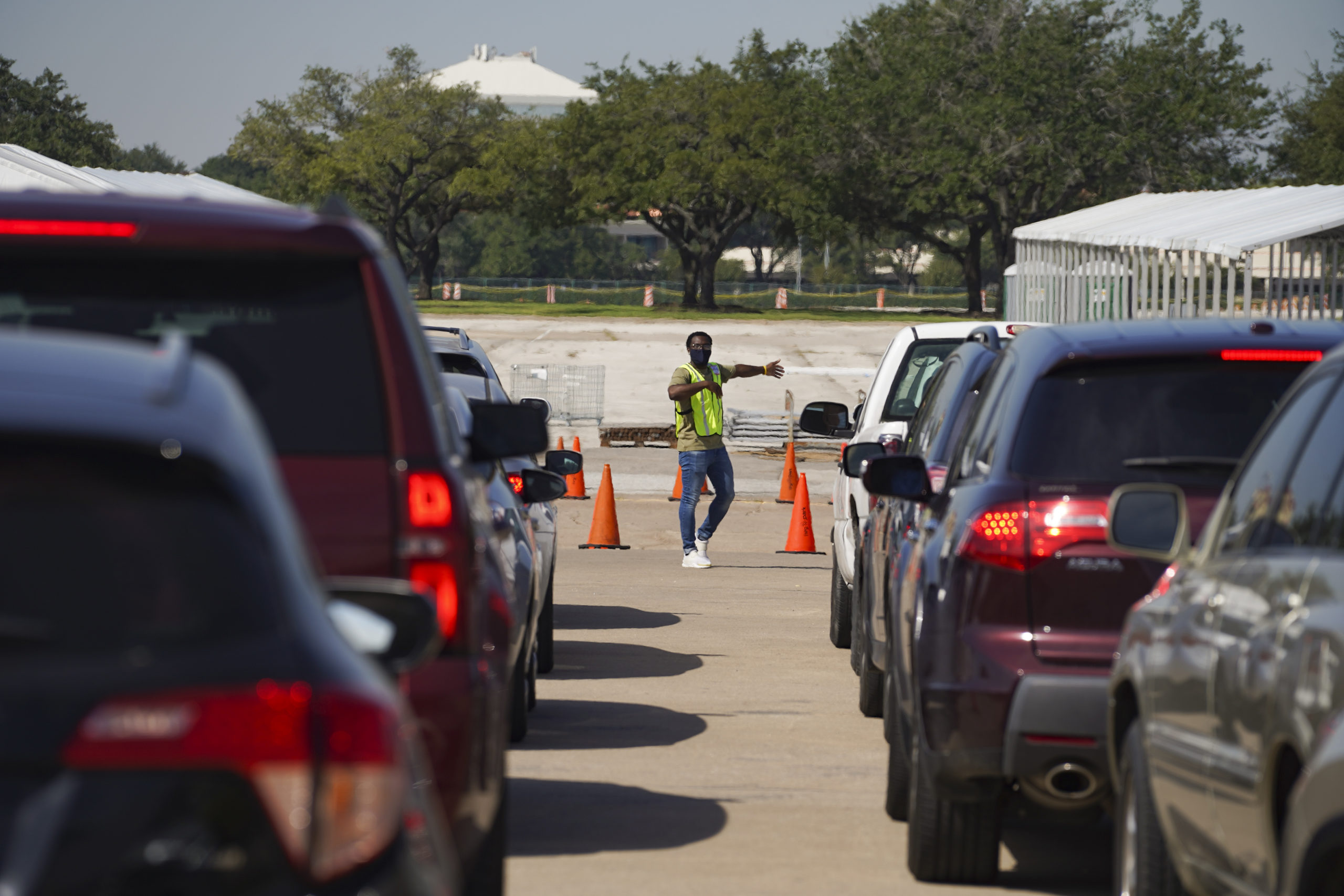 HOUSTON, TX - OCTOBER 07: An election worker guides voters in cars at a drive-through mail ballot drop-off site at NRG Stadium on October 7, 2020 in Houston, Texas. Gov. Gregg Abbott issued an executive order limiting each county to one mail ballot drop-off site due to the pandemic. (Photo by Go Nakamura/Getty Images)