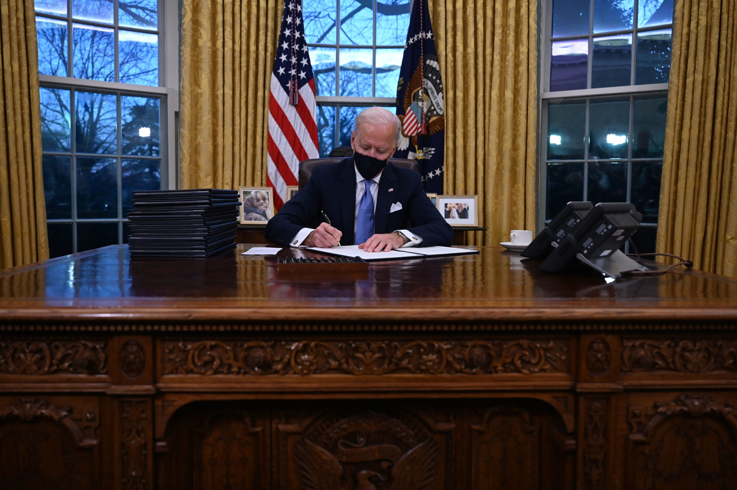 President Joe Biden signs a series of executive orders in the Oval Office on Jan. 20. (Jim Watson/AFP via Getty Images)