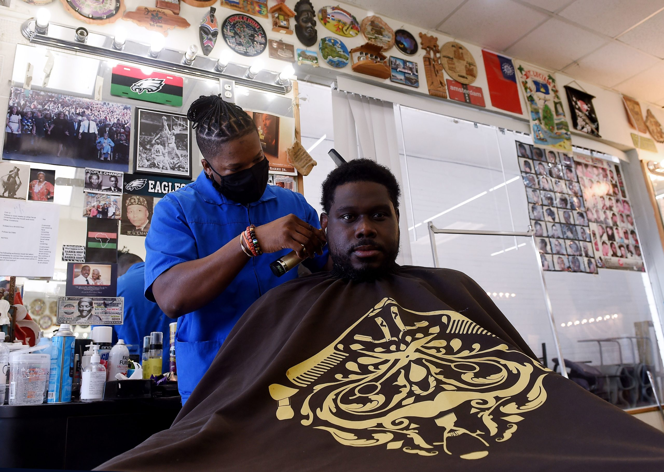 Russel, a barber working for The Shop Hair Spa, cuts the hair of a customer, in Hyattsville, Maryland on February 25, 2021. - Barber Mike Brown carefully guides his trimmer as he fights misconceptions about Covid-19 among his African-American customers, who face an outsize risk from the virus but are less likely to get vaccinated against it. (OLIVIER DOULIERY/AFP via Getty Images)