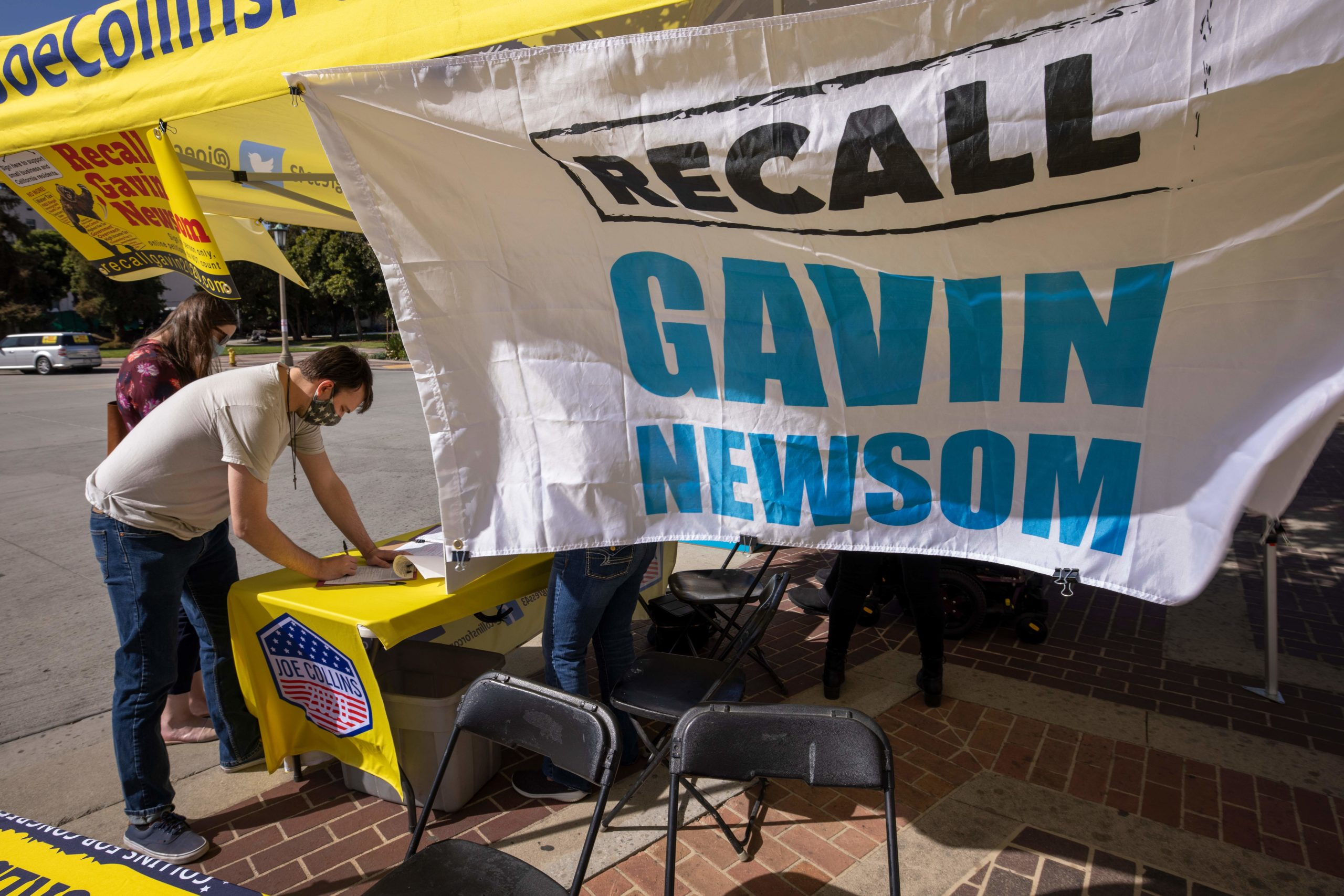 A man signs a petition as conservative activists gather signatures in a recall effort against California Governor Gavin Newsom (Photo by DAVID MCNEW/AFP via Getty Images)