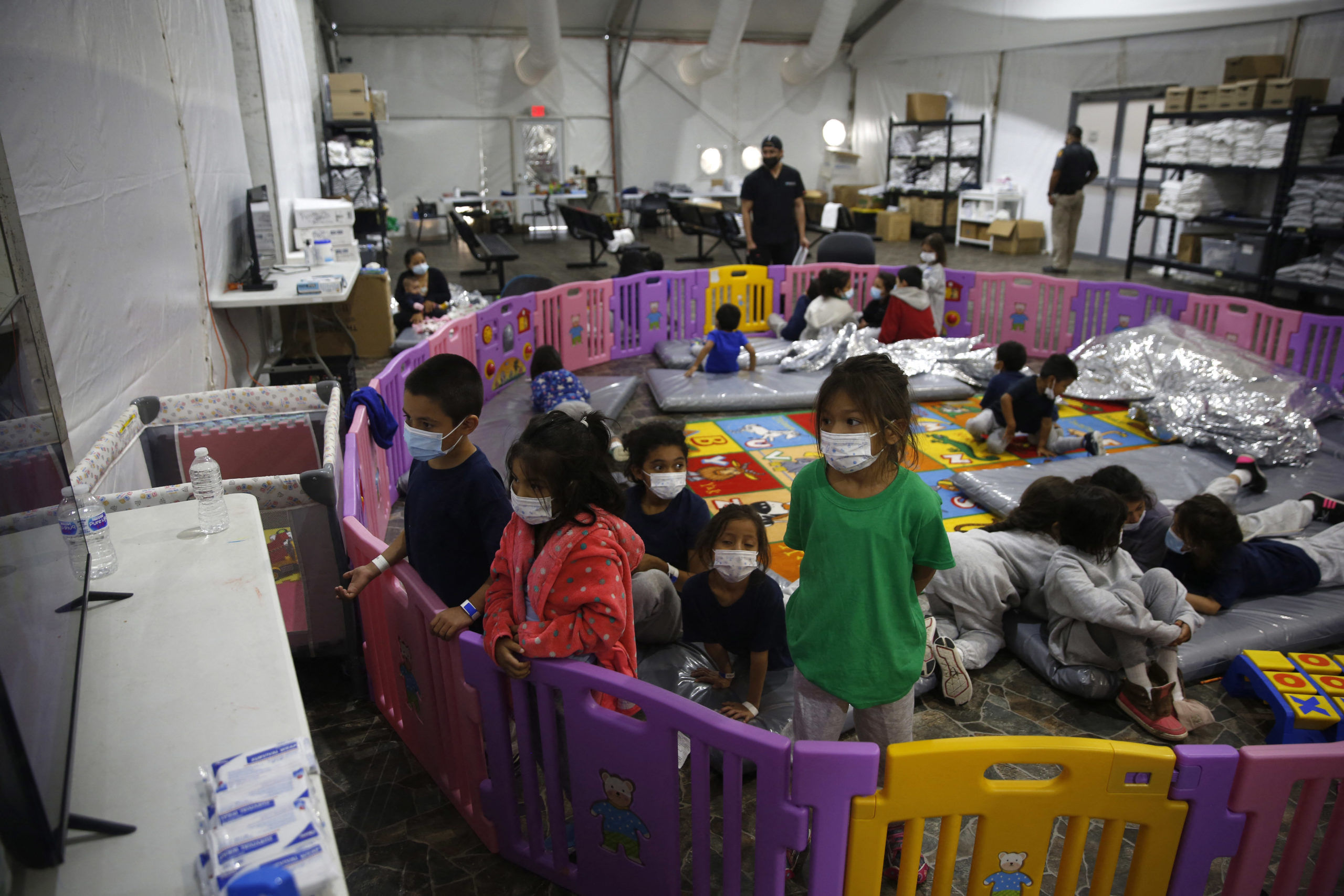 Young unaccompanied migrants, ages 3-9 watch TV inside a playpen at the Donna Department of Homeland Security holding facility (Photo by DARIO LOPEZ-MILLS/POOL/AFP via Getty Images)