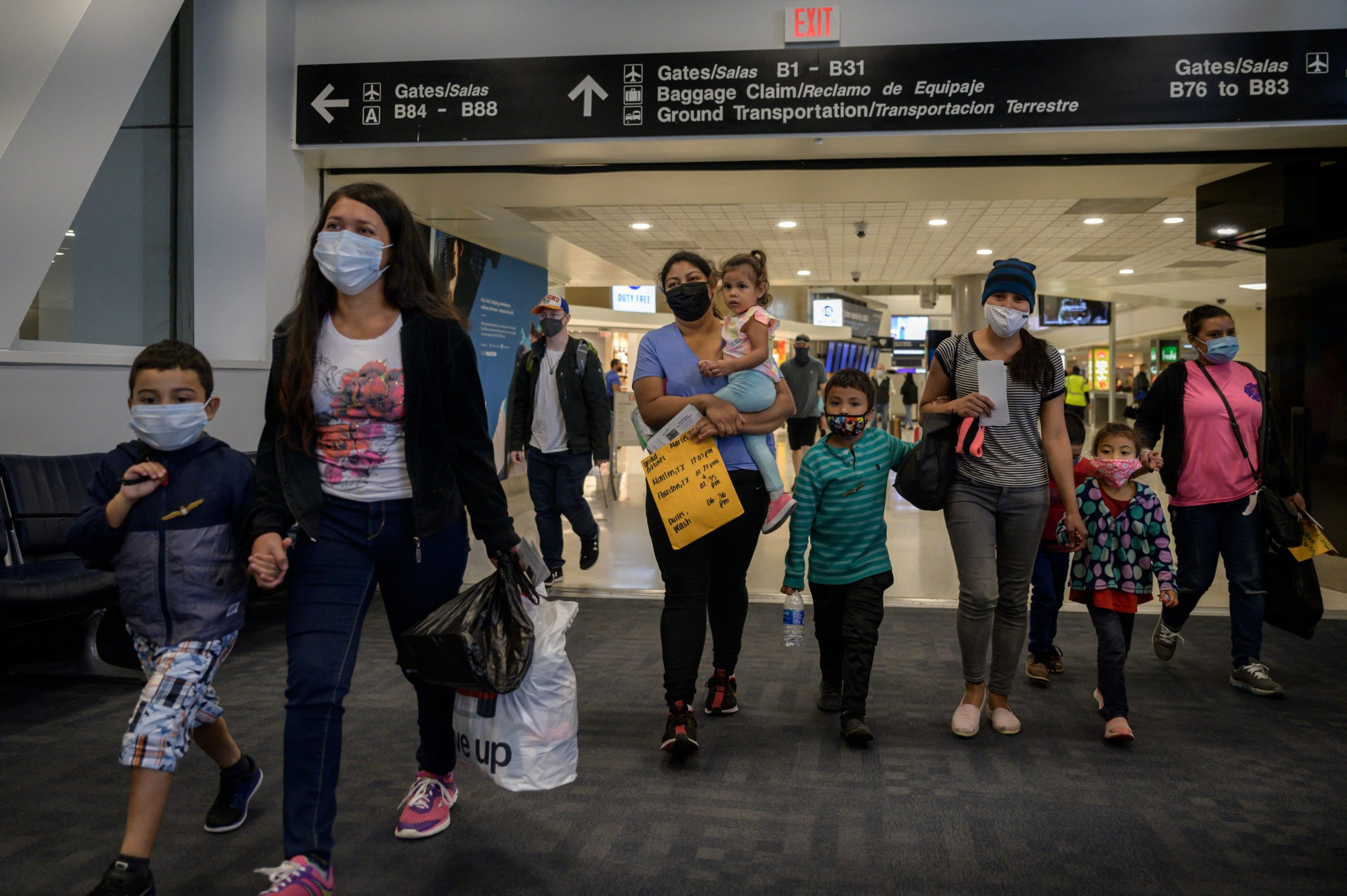 Dania (2nd L) and her son Daniel (L) from Honduras walk with mother Reina (3rd R) and her children Diana (2nd R) and Dariel (4th R) from El Salvador, through Houston airport during a transfer on March 30, 2021. (Photo by ED JONES/AFP via Getty Images)