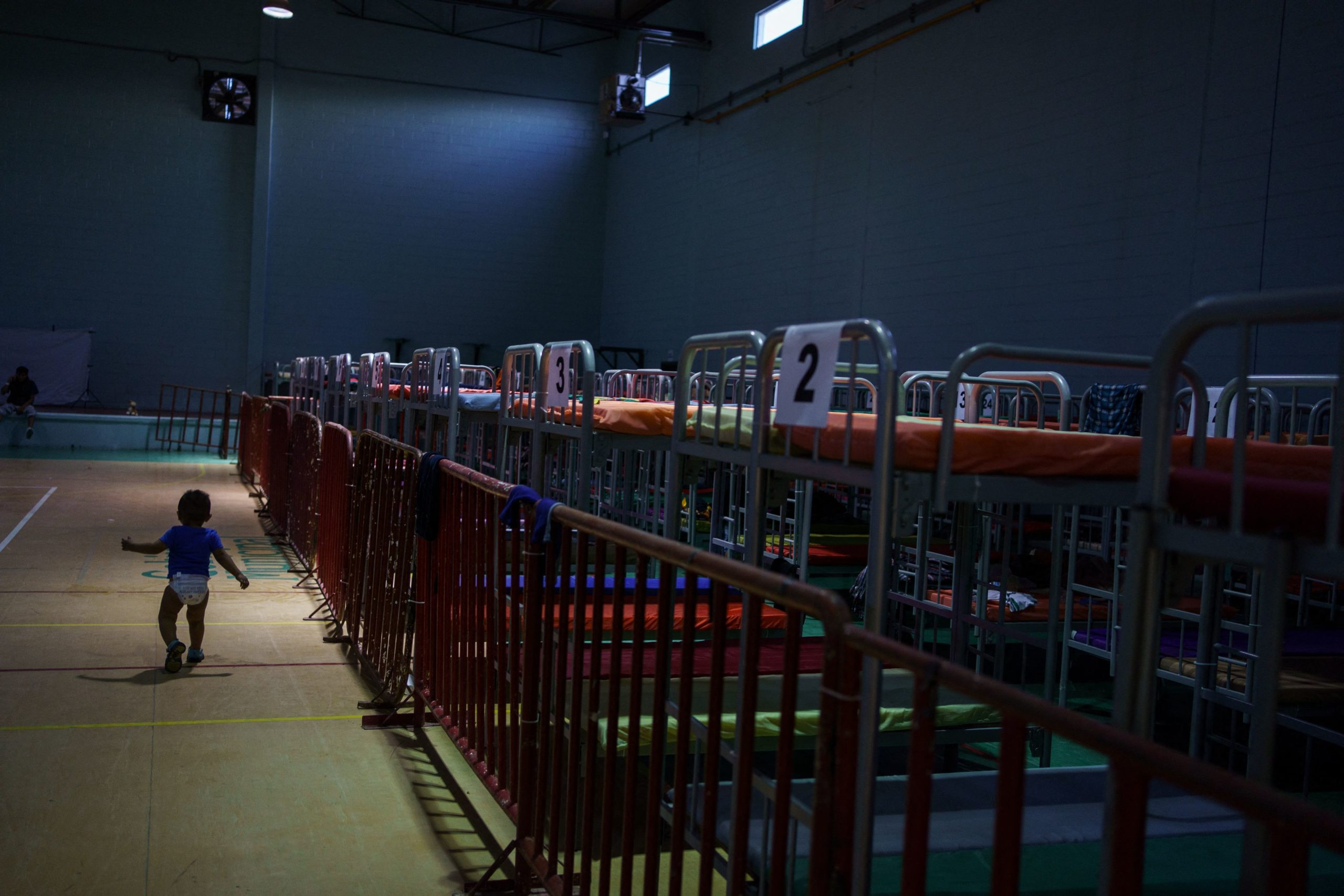 A child walks by bunk beds at Gimnasio Kiki Romero, a gym which has been converted into a makeshift migrant shelter in Ciudad Juarez on April 6, 2021.(Photo by PAUL RATJE/AFP via Getty Images)