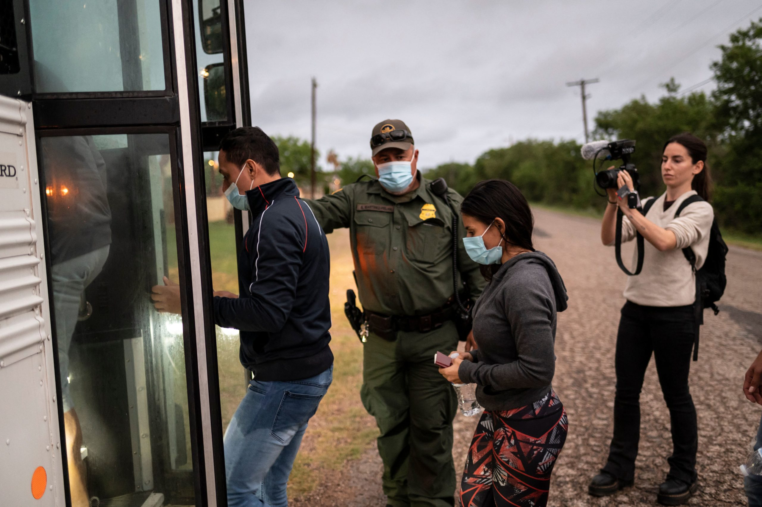 Migrants make their onto a bus after being apprehended near the border between Mexico and the United States in Del Rio, Texas on May 16, 2021. (Photo by SERGIO FLORES/AFP via Getty Images)