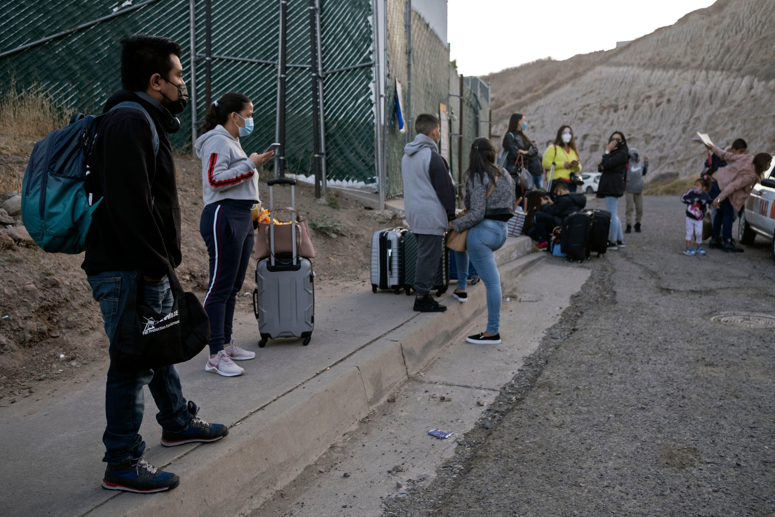 Cruz Estuardo Tunpumay (L), a 32 year-old migrant from Guatemala, stands a with other asylum seekers while waiting to enter a Mexican Government facility they will be examined before being taken to the border by UNHCR and Mexican authorities in Tijuana, Baja California state, Mexico on May 20, 2021. (Photo by Guillermo Arias / AFP) (Photo by GUILLERMO ARIAS/AFP via Getty Images)