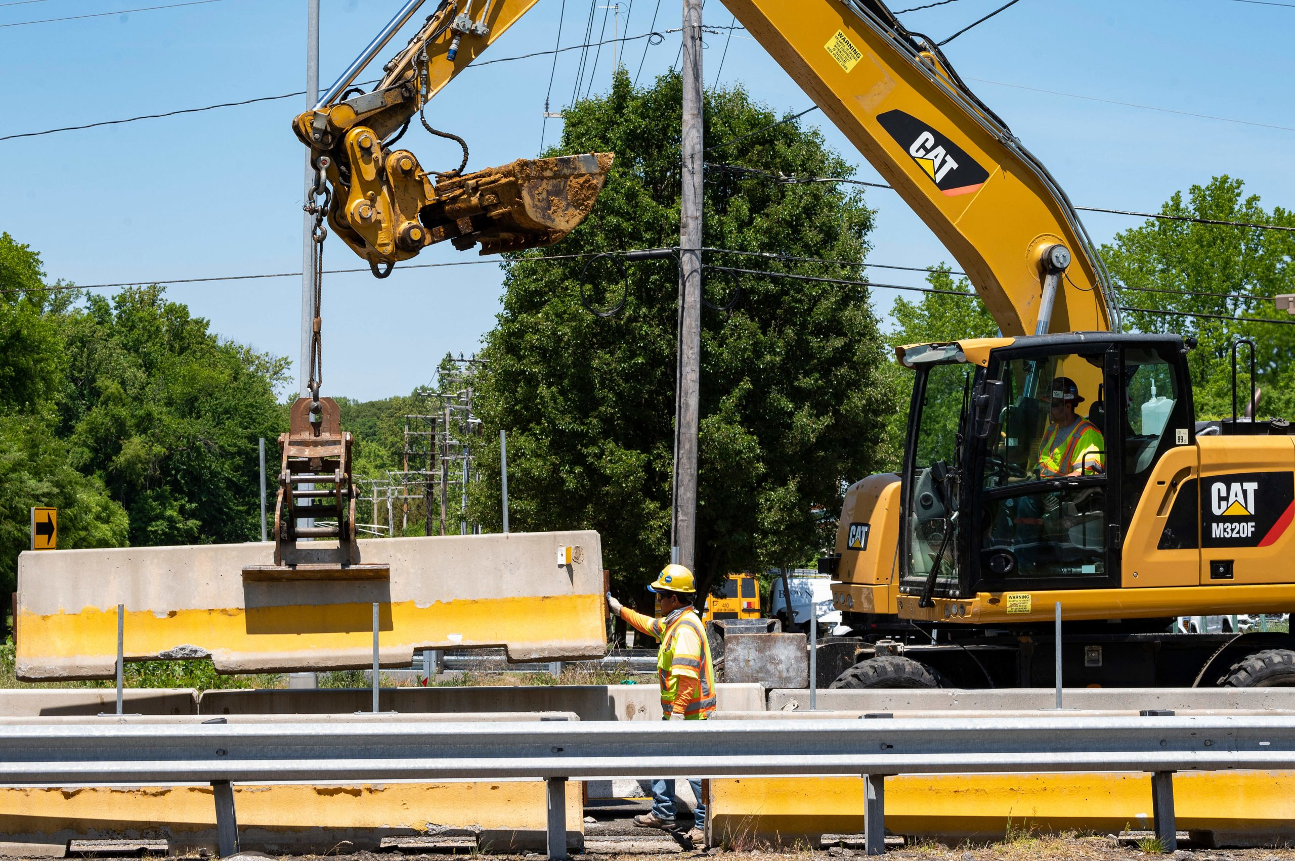 Construction workers move road barriers into place at a project site in Annapolis, Maryland on May 21. (Jim Watson/AFP via Getty Images)