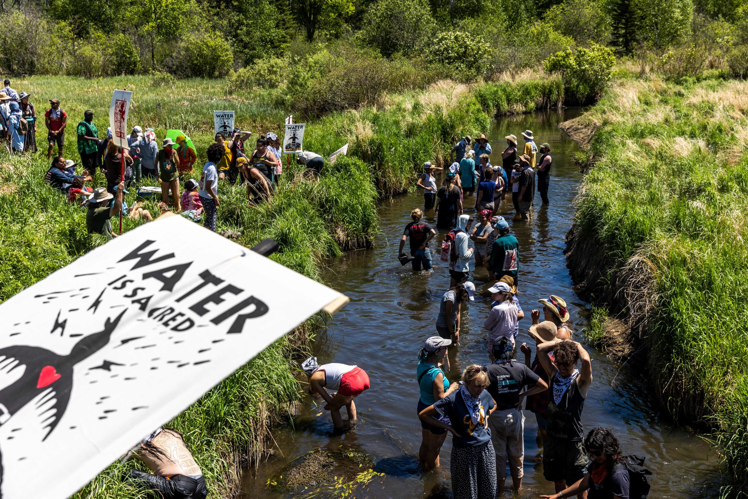 Climate activist and Indigenous community members gather on the river for a traditional water ceremony during a rally and march to protest the construction of Enbridge Line 3 pipeline in Solvay, Minnesota on June 7, 2021. - Line 3 is an oil sands pipeline which runs from Hardisty, Alberta, Canada to Superior, Wisconsin in the United States. In 2014, a new route for the Line 3 pipeline was proposed to allow an increased volume of oil to be transported daily. While that project has been approved in Canada, Wisconsin, and North Dakota, it has sparked continued resistance from climate justice groups and Native American communities in Minnesota. While many people are concerned about potential oil spills along Line 3, some Native American communities in Minnesota have opposed the project on the basis of treaty rights and calling President Biden to revoke the permits and halt construction. (Photo by Kerem Yucel / AFP) (Photo by KEREM YUCEL/AFP via Getty Images)