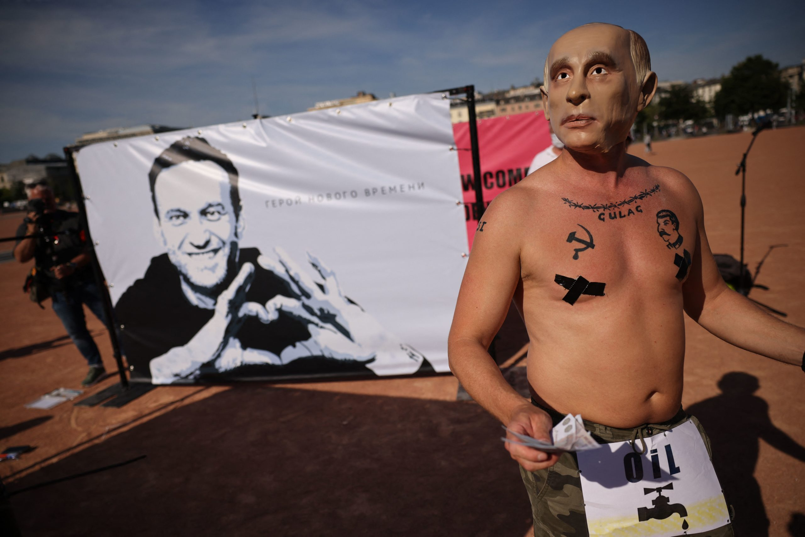 A demonstrator protests in front of a banner in support to Kremlin critic Alexei Navalny reading