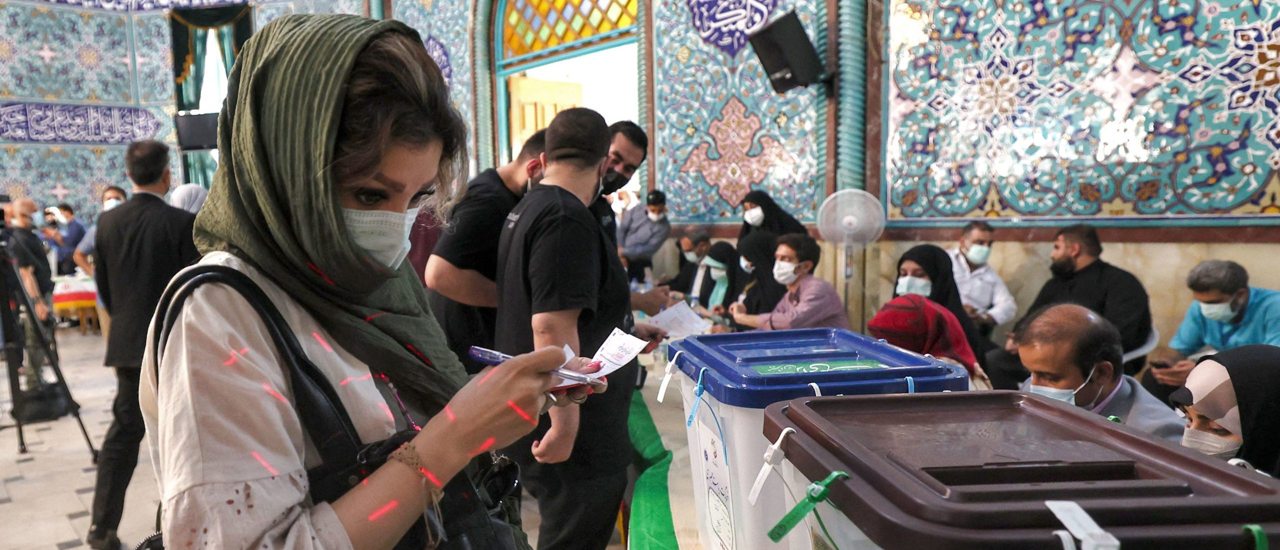 A woman examines a ballot before casting it at a polling station in Iran's capital Tehran on June 18, 2021, during the 2021 presidential election. - Iranians voted on June 18 in a presidential election in which ultraconservative cleric Ebrahim Raisi is seen as all but certain to coast to victory after all serious rivals were barred from running. (Photo by ATTA KENARE/AFP via Getty Images)