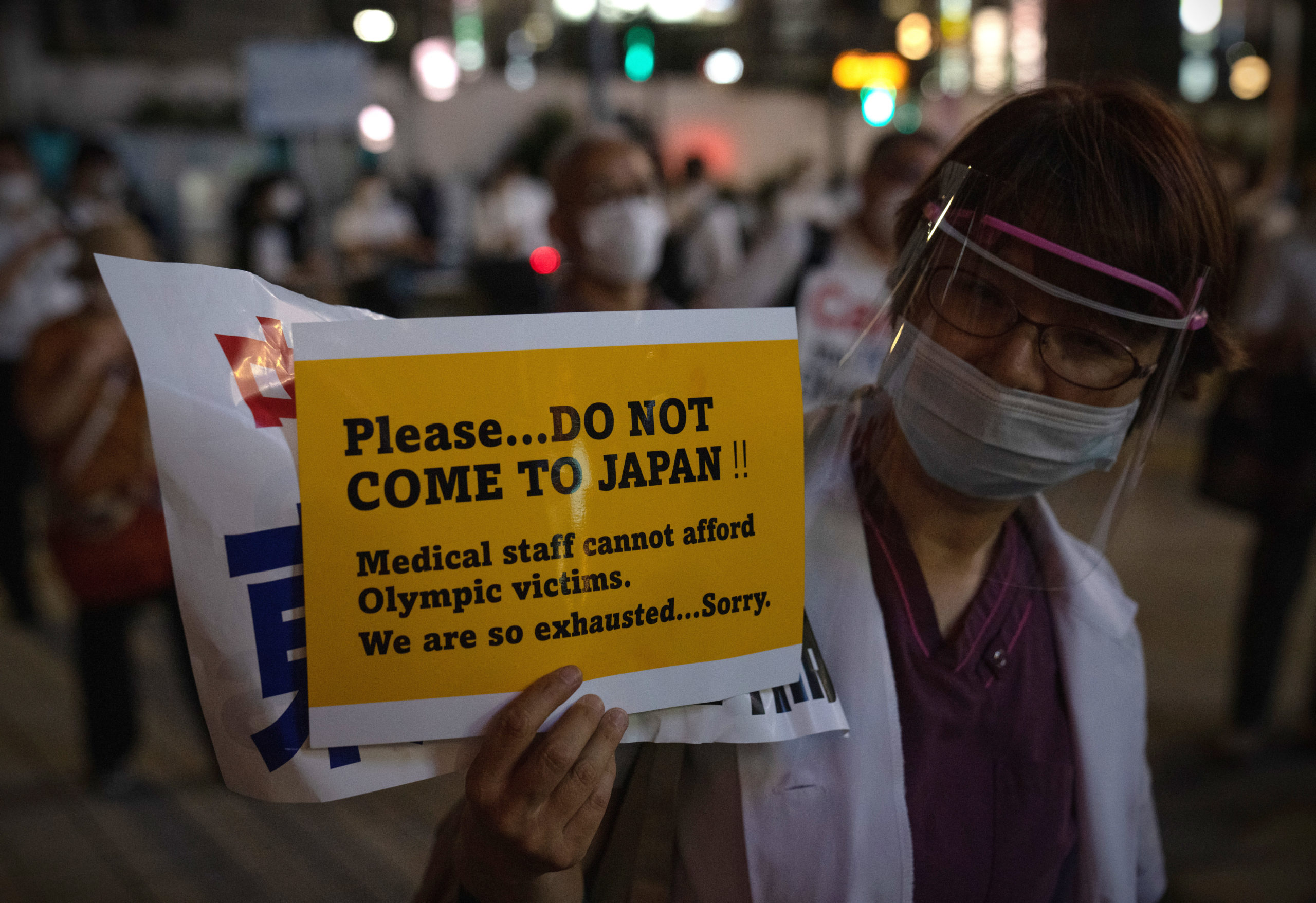 A doctor holds up a poster asking people not to come to Japan for the Olympics during a protest against the Olympic Games on June 23, 2021 in Tokyo, Japan. Protests have continued to take place in the run up to the Olympics amid concern over the safety of holding the Games during the global coronavirus pandemic. (Photo by Carl Court/Getty Images)