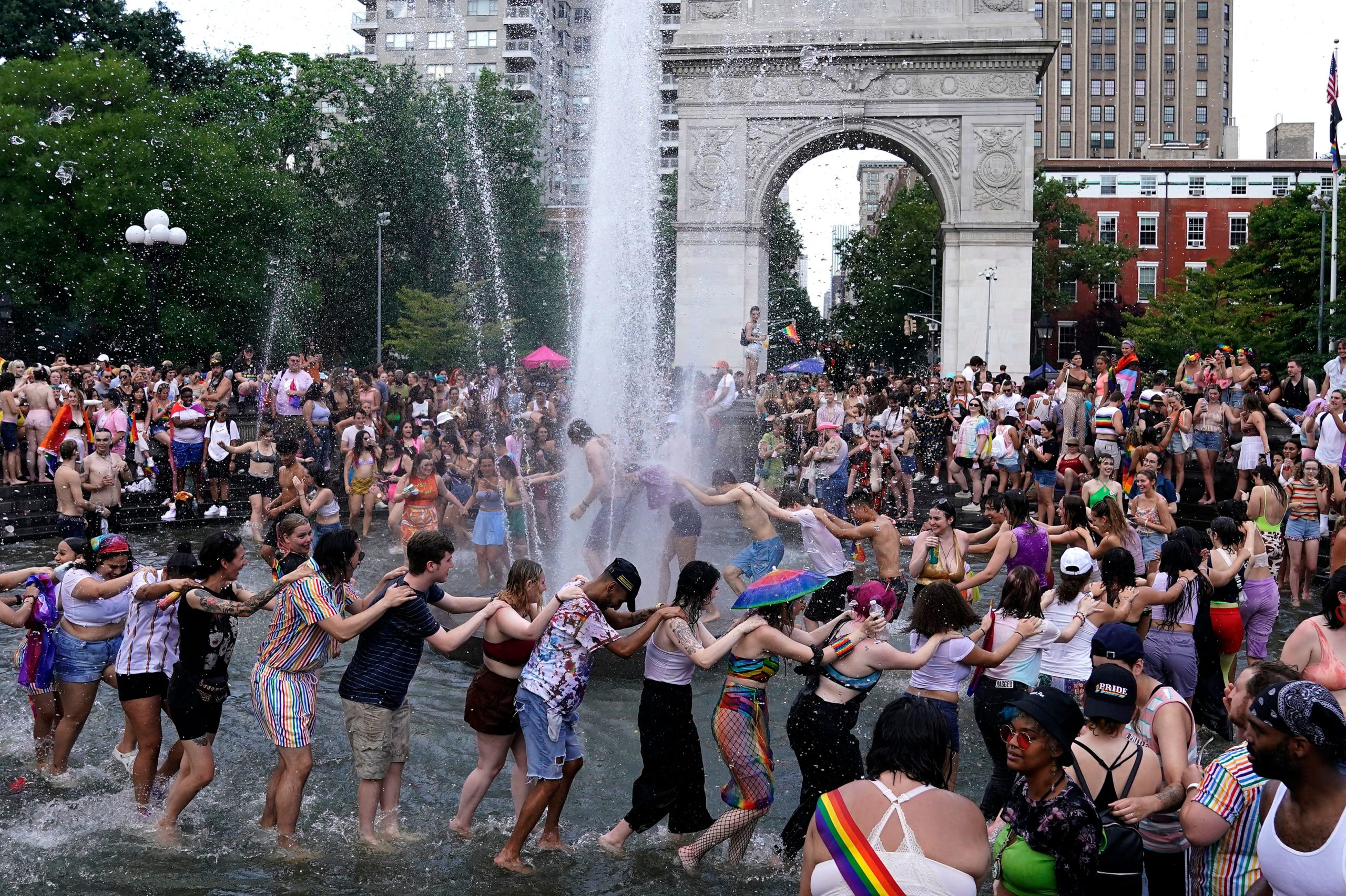 People dance in the Washington Square Fountain during the 3rd annual Queer Liberation March in New York June 27, 2021. (Photo by TIMOTHY A. CLARY/AFP via Getty Images)