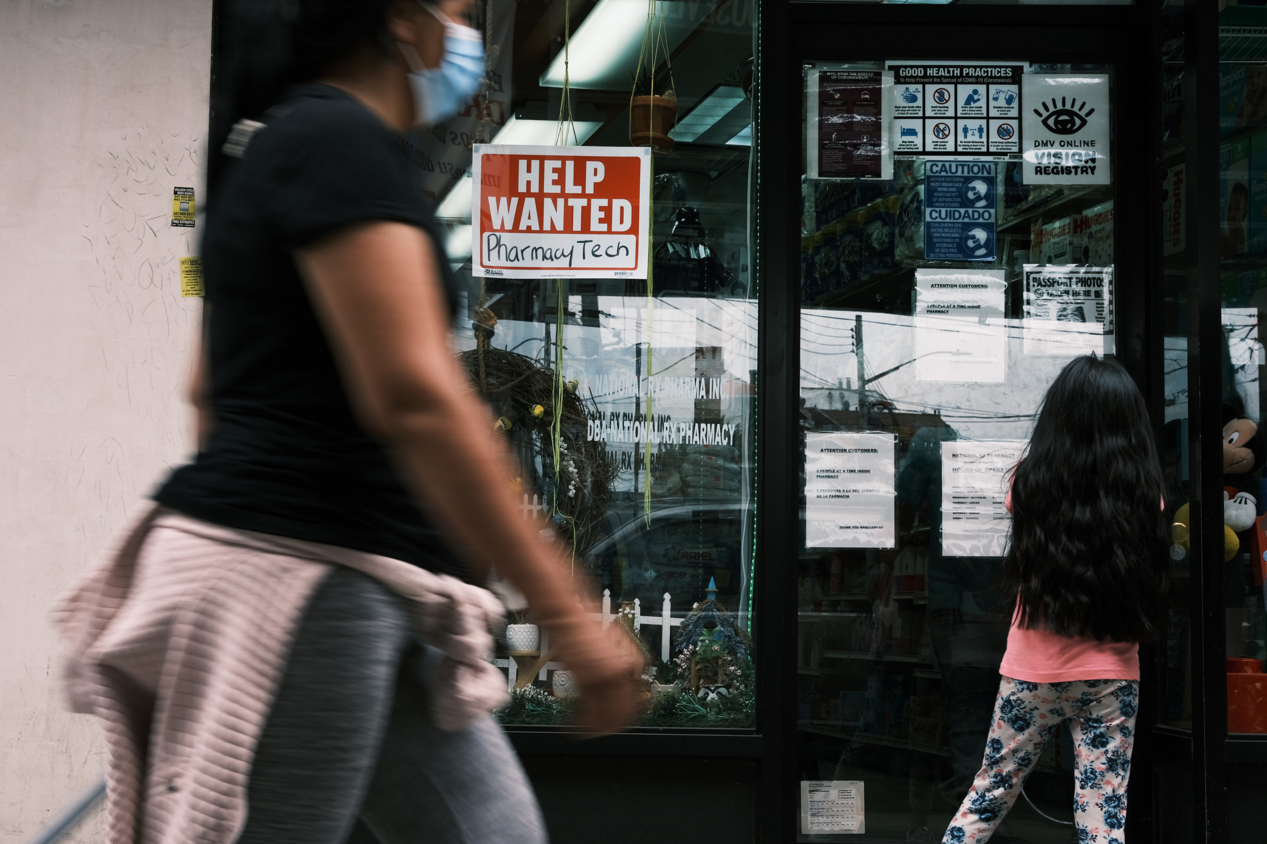 """People walk by a """"Help Wanted"""" sign in the Queens borough of New York City on June 4. (Spencer Platt/Getty Images)"""