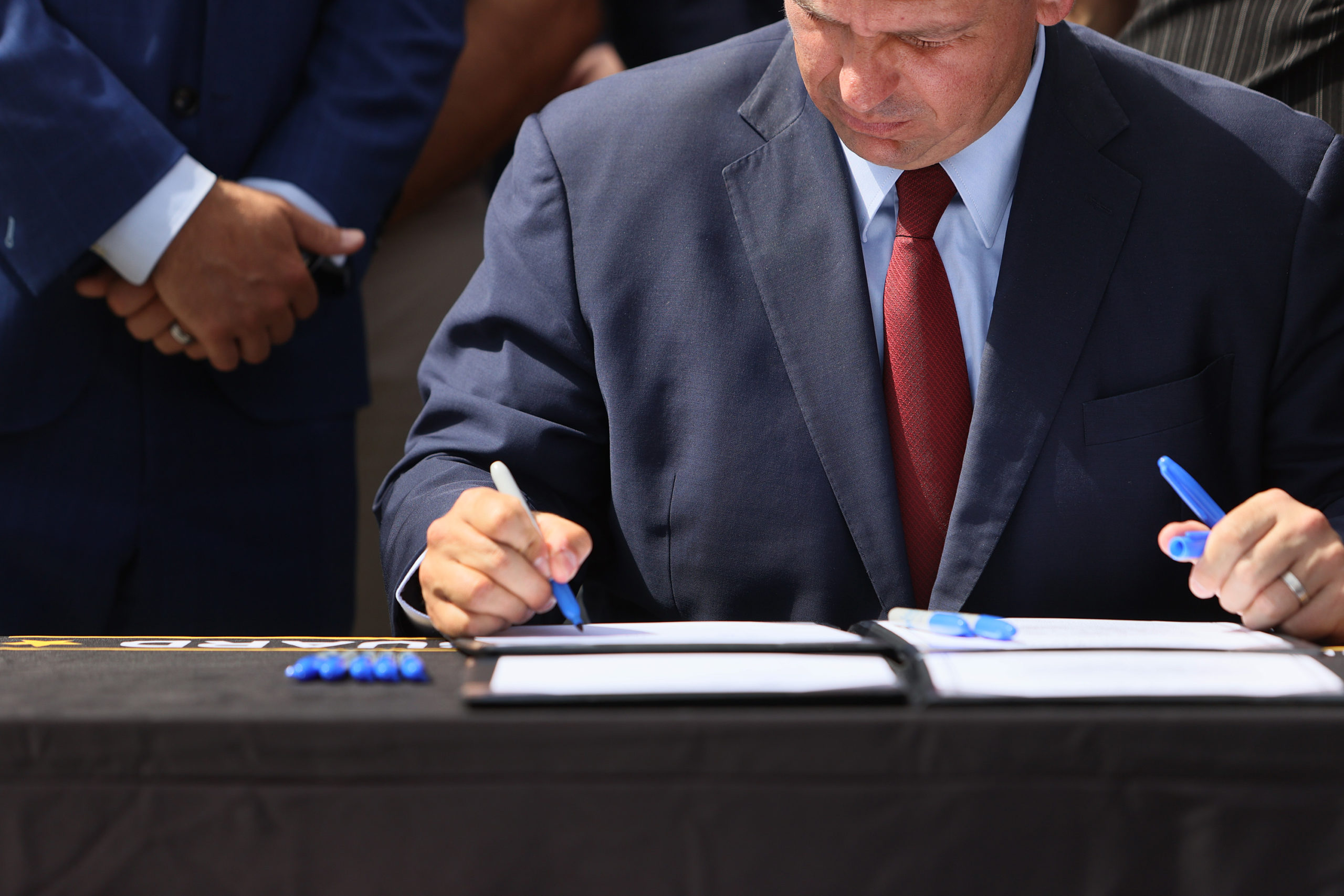 Florida Gov. Ron DeSantis signs two bills surrounded by officials on June 7 in Miami, Florida. (Joe Raedle/Getty Images)