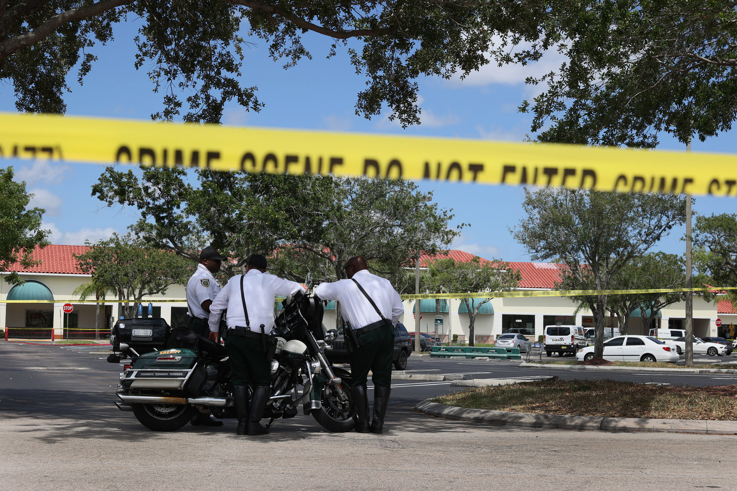 ROYAL PALM BEACH, FLORIDA - JUNE 10: Palm Beach County Sheriff's officers stand outside of a Publix supermarket where a woman, child and a man were found shot to death on June 10, 2021 in Royal Palm Beach, Florida. Law enforcement officials continue to investigate the crime scene for clues as to why the shooting occurred. (Photo by Joe Raedle/Getty Images)