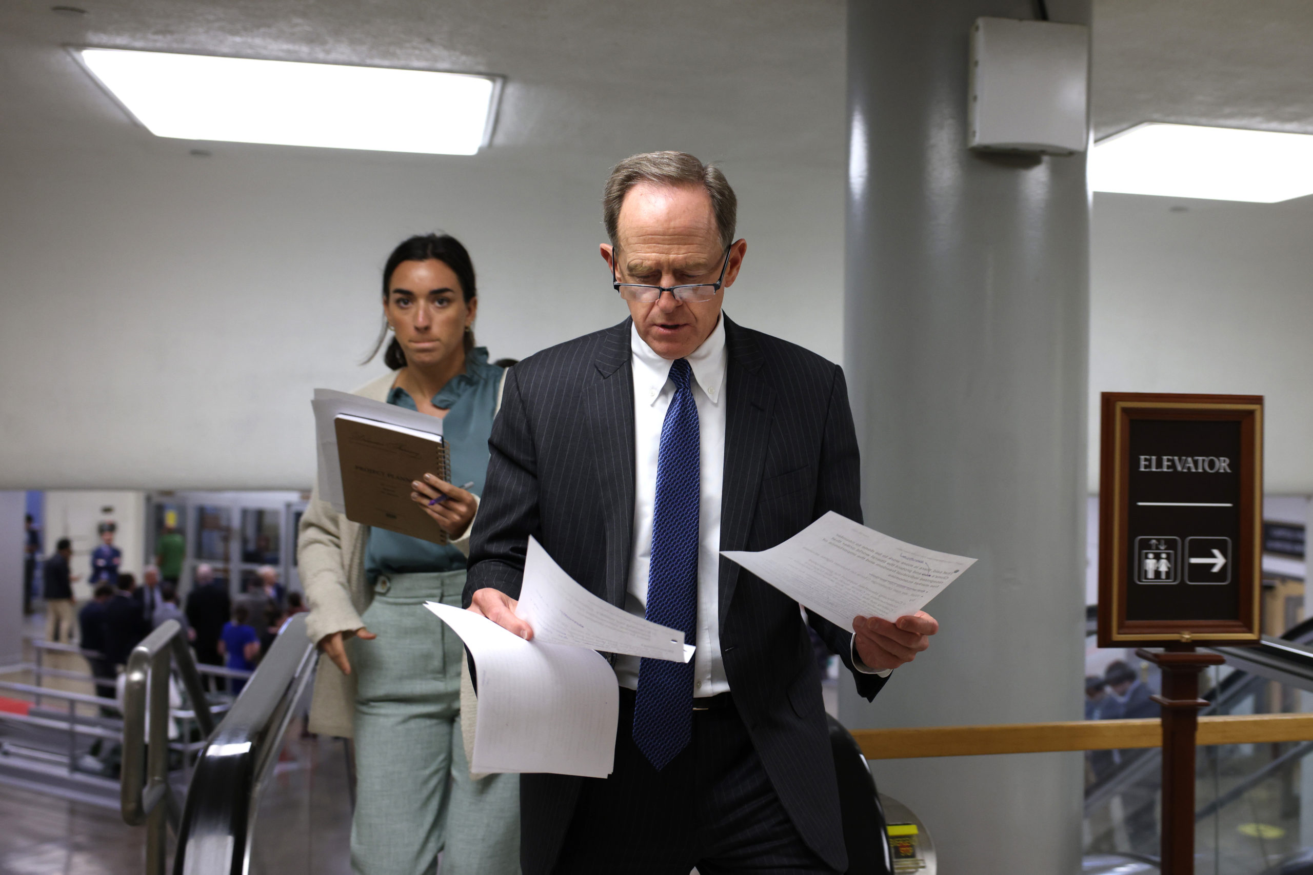 Republican Sen. Pat Toomey looks through documents as he walks on Tuesday. (Anna Moneymaker/Getty Images)