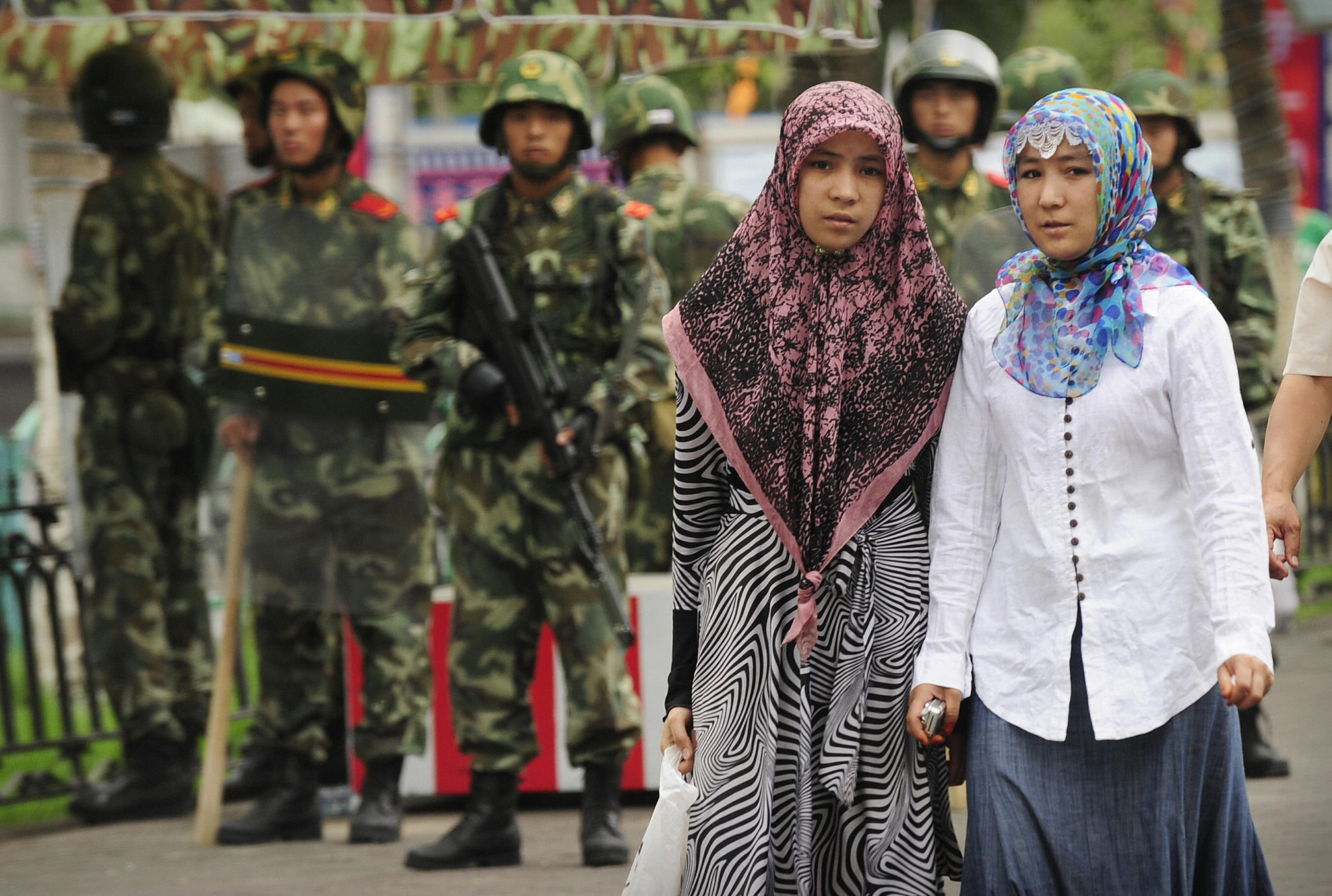 Two ethnic Uighur women pass Chinese paramilitary policemen standing guard outside the Grand Bazaar in the Uighur district of the city of Urumqi in China's Xinjiang region on July 14, 2009. (PETER PARKS/AFP via Getty Images)