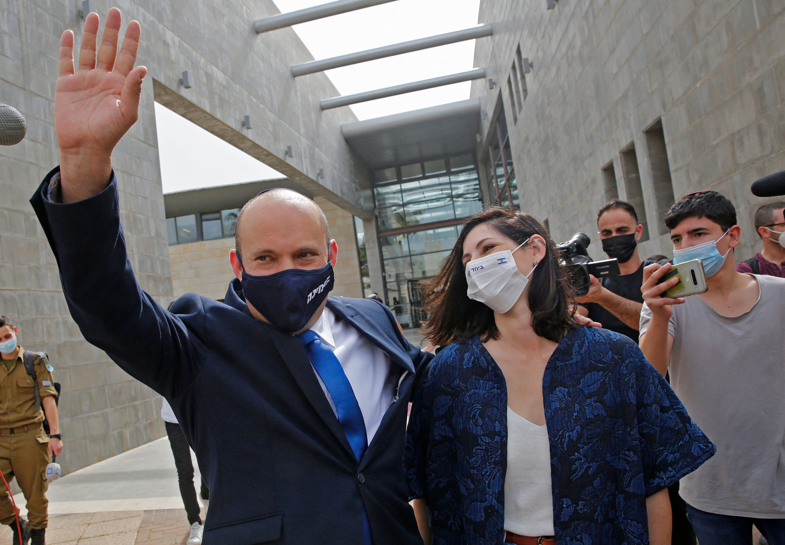 Israel's Naftali Bennett, leader of the right wing 'New Right' Yamina party, waves as he walks with his wife Gilat at a polling station where they voted on March 23, 2021 in the city of Raanana in the fourth national election in two years. (Photo by GIL COHEN-MAGEN/AFP via Getty Images)