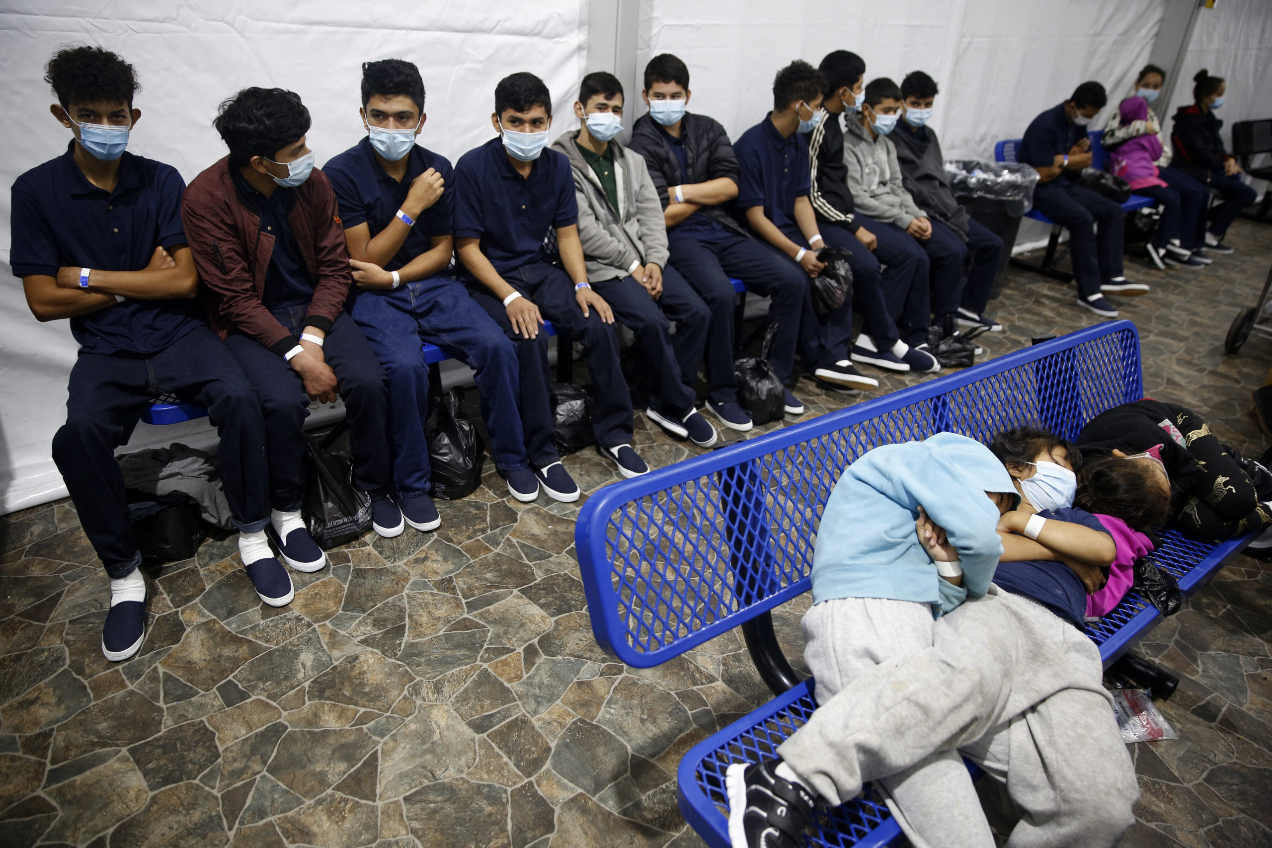 Young migrants wait for processing inside the Donna Department of Homeland Security holding facility. (Photo by DARIO LOPEZ-MILLS/POOL/AFP via Getty Images)