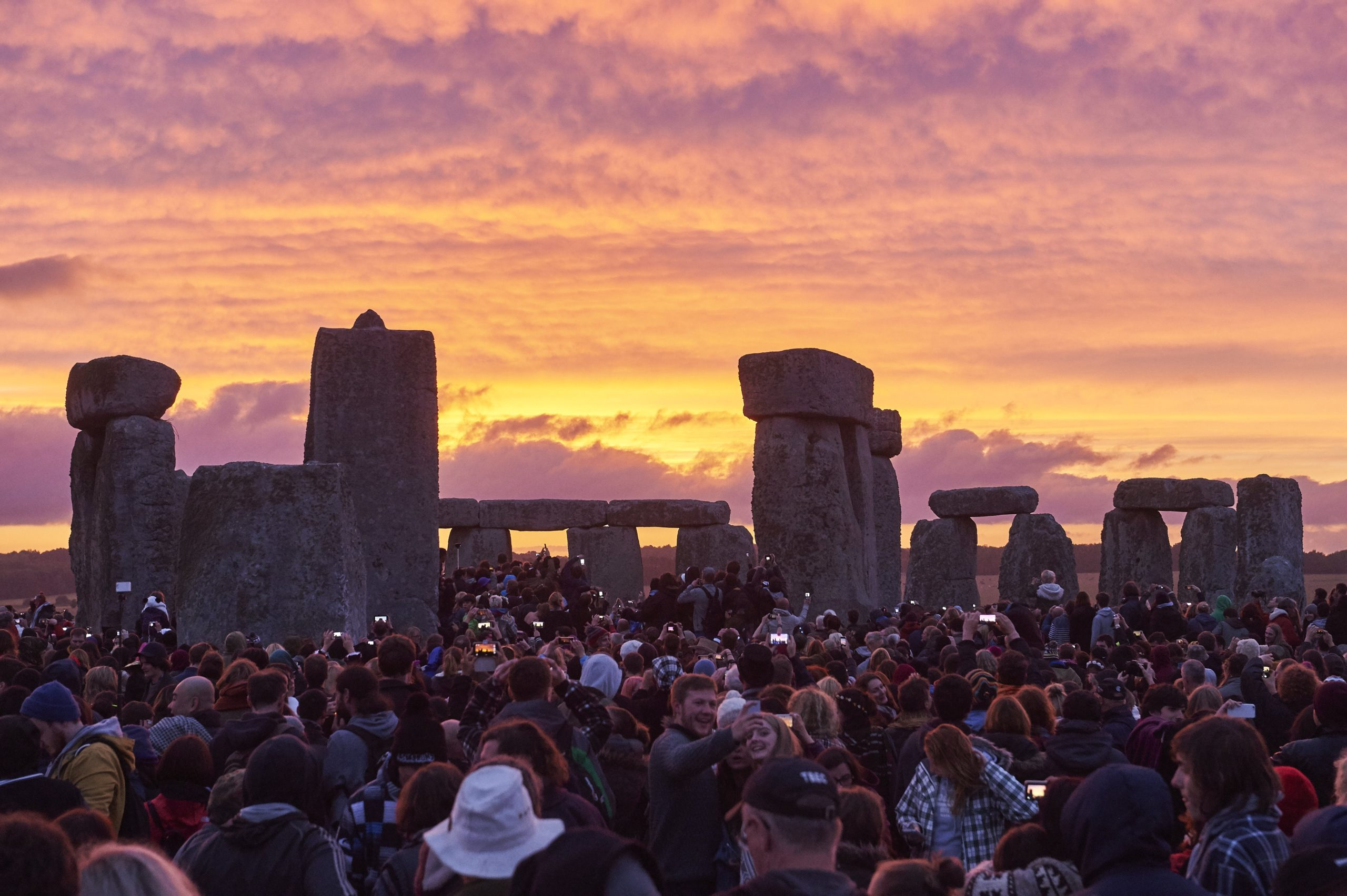 Revellers watch the sunrise as they celebrate the pagan festival of Summer Solstice at Stonehenge in Wiltshire, southern England on June 21, 2015. (NIKLAS HALLE'N/AFP via Getty Images)