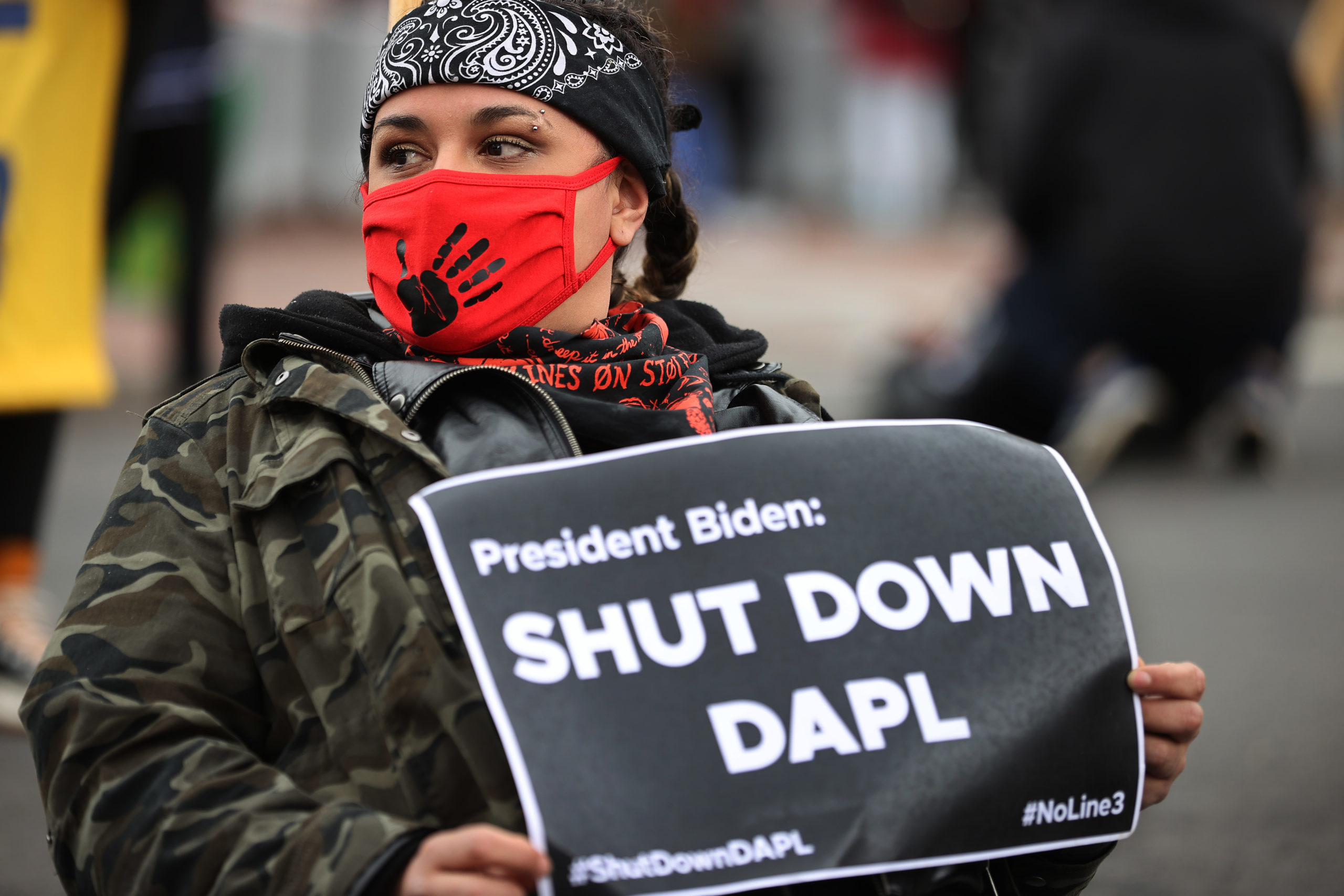 An indigenous environmental activist attaches herself to a large tripod using a bike lock, blocking traffic near Black Lives Matter Plaza on the north side of the White House as part of a protest against oil pipelines April 01, 2021 in Washington, DC. (Photo by Chip Somodevilla/Getty Images)