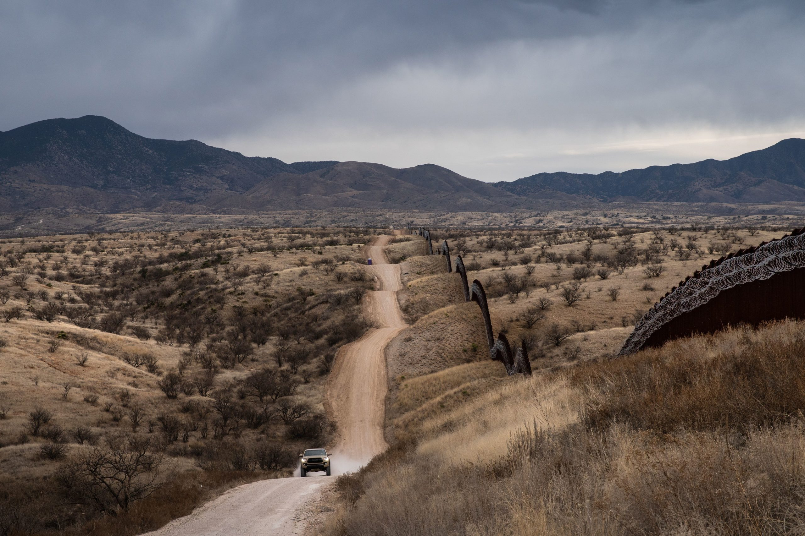 A car speeds by the US border fence, covered in barbed wire and concertina wire, separating the US and Mexico, at the outskirts of Nogales, Arizona, on February 9, 2019. (Photo by Ariana Drehsler / AFP) (Photo by ARIANA DREHSLER/AFP via Getty Images)