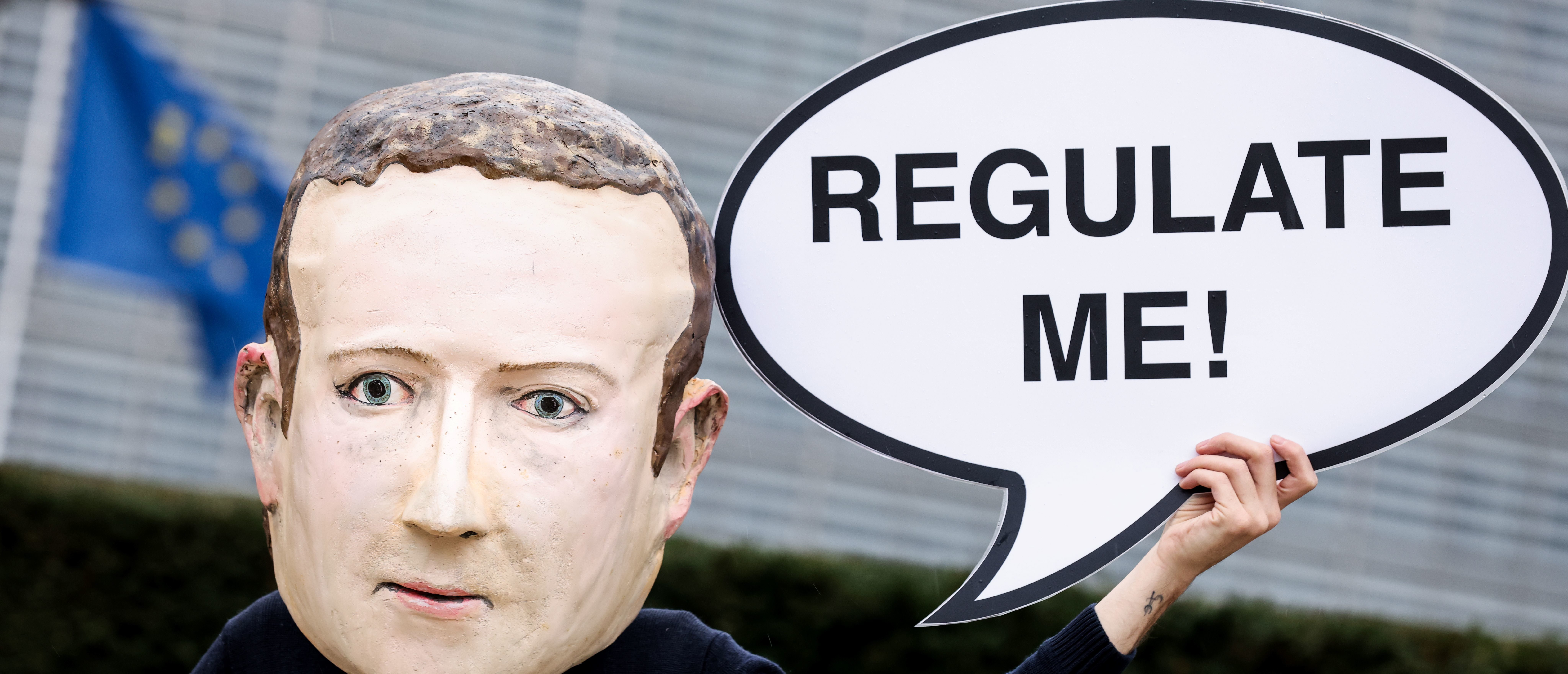 """An activist of environmental NGO Avaaz wearing a mask depicting Facebook CEO Mark Zuckerberg holds a banner reading """"Regulate me"""" during an action marking the release of the Digital Services Act, outside the European Commission building in Brussels on December 15, 2020. (Photo by KENZO TRIBOUILLARD/AFP via Getty Images)"""