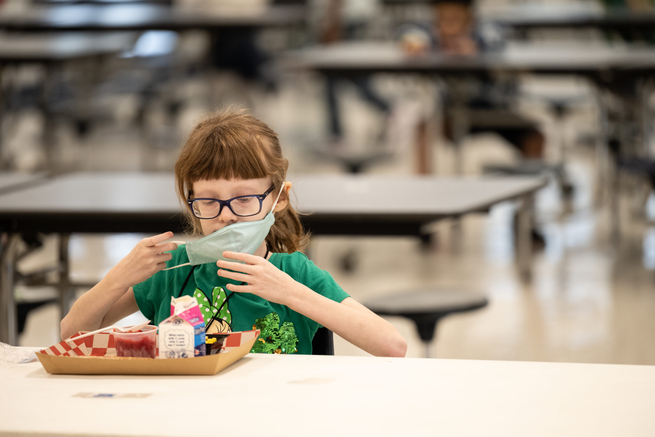 LOUISVILLE, KY - MARCH 17: A child puts her mask back on after finishing lunch at a socially distanced table in the cafeteria of Medora Elementary School on March 17, 2021 in Louisville, Kentucky. Today marks the reopening of Jefferson County Public Schools for in-person learning with new COVID-19 procedures in place. (Photo by Jon Cherry/Getty Images)