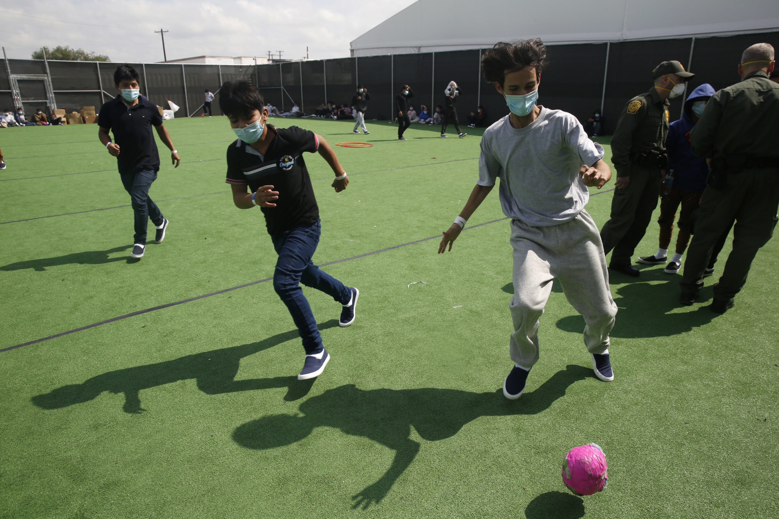 Minors play soccer on a field at the Department of Homeland Security holding facility run by the Customs and Border Patrol (CBP) on March 30, 2021 in Donna, Texas. (Photo by Dario Lopez-Mills - Pool/Getty Images)