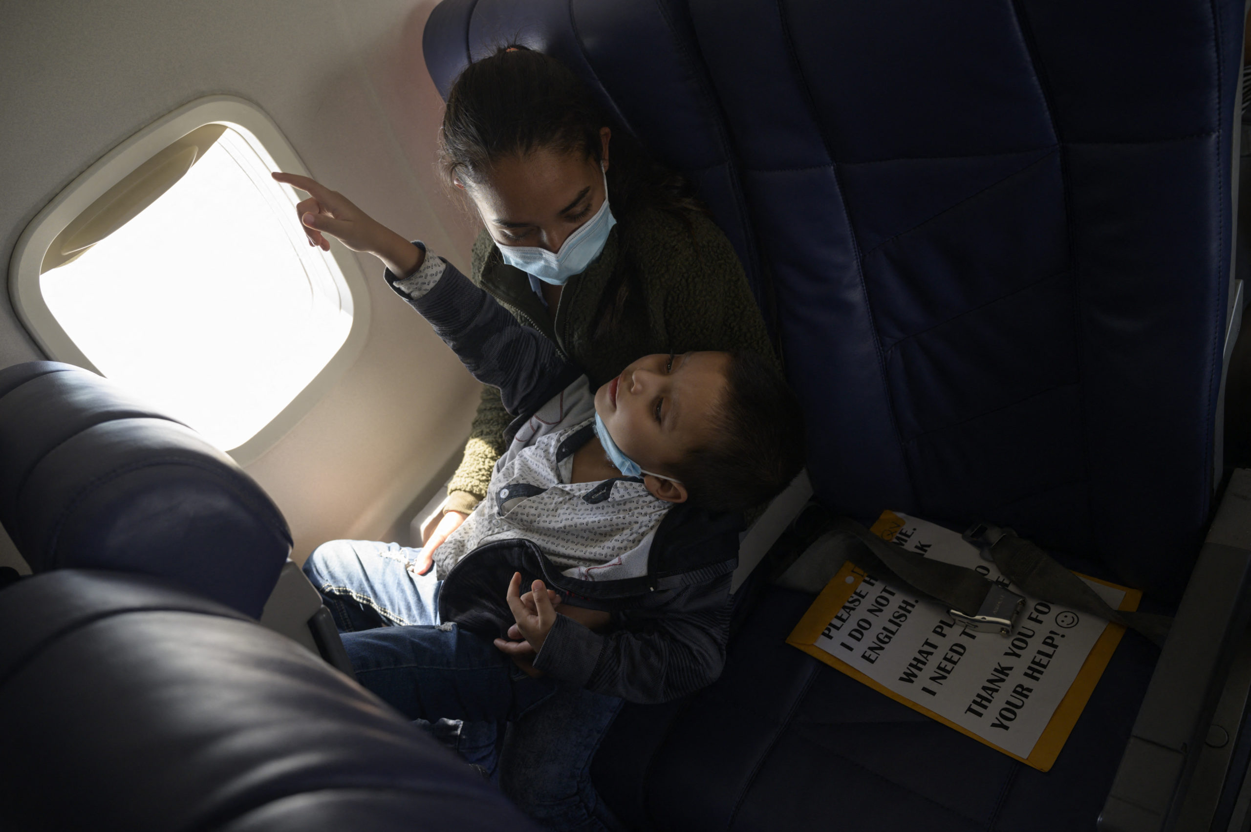 Central American migrants Lidia and her son Isaac sit aboard their flight on March 30, 2021 from McAllen to Houston after being released from a US government holding facility for illegal migrants seeking asylum in McAllen, Texas. (Photo by Ed JONES / AFP) (Photo by ED JONES/AFP via Getty Images)